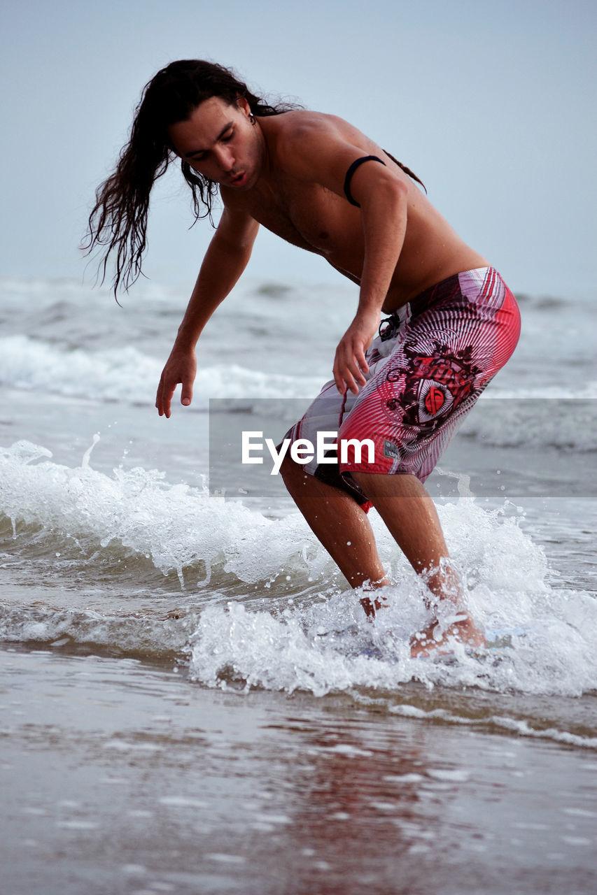 Shirtless Young Man On Surfboard At Sea Shore