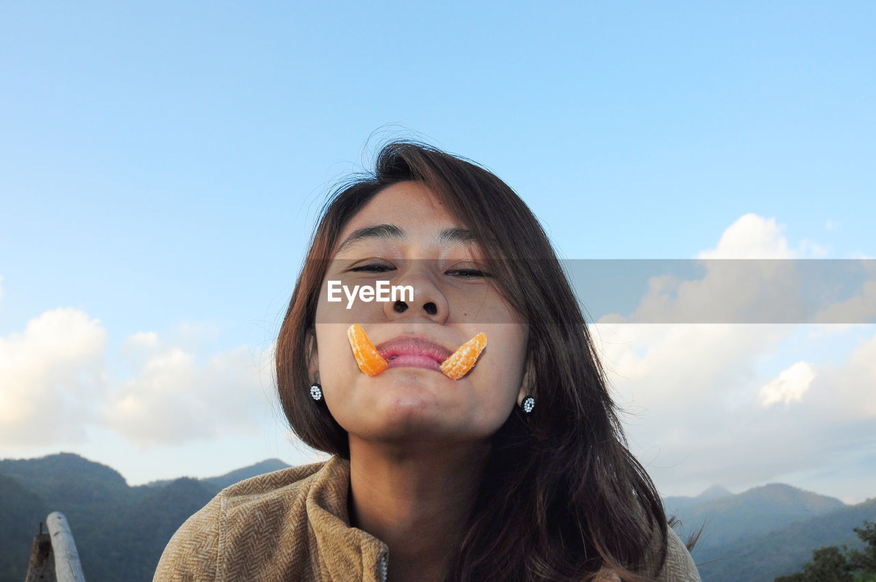 Portrait of woman with orange slices in mouth against sky
