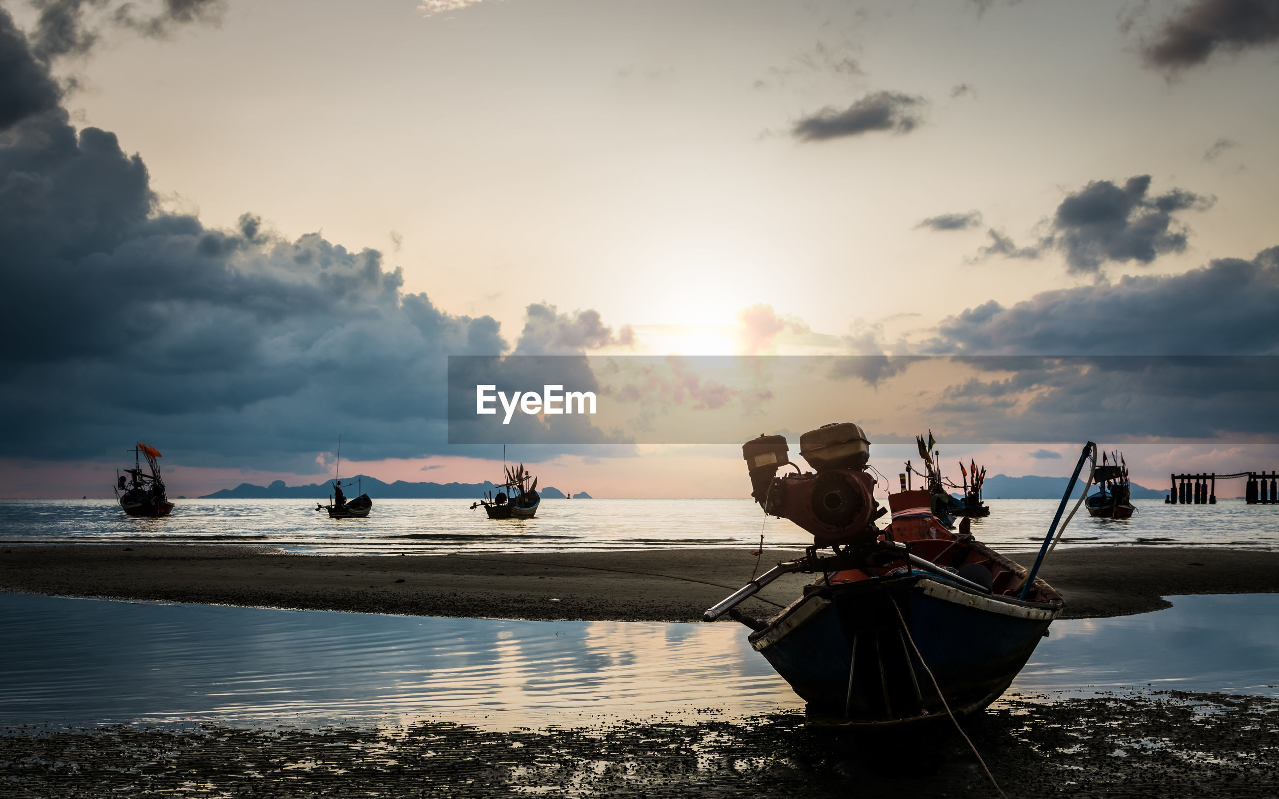 Many fishing boat in the sea when low tide under the sun
