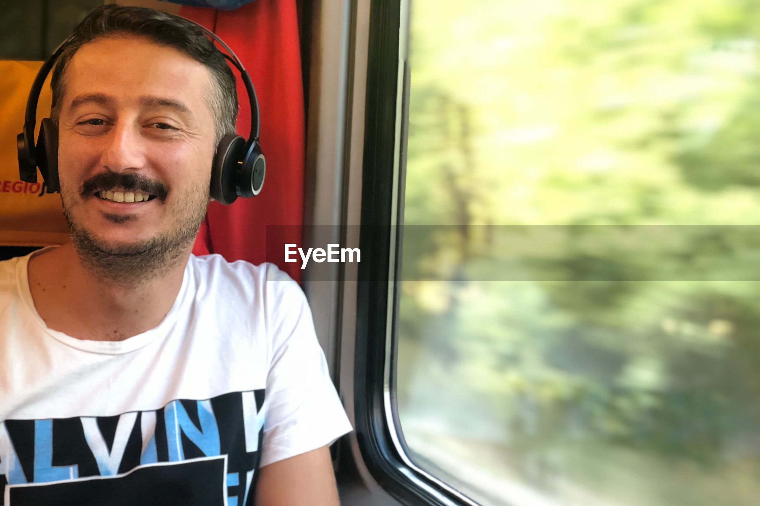 Portrait of smiling mid adult man listening music while sitting by window in train