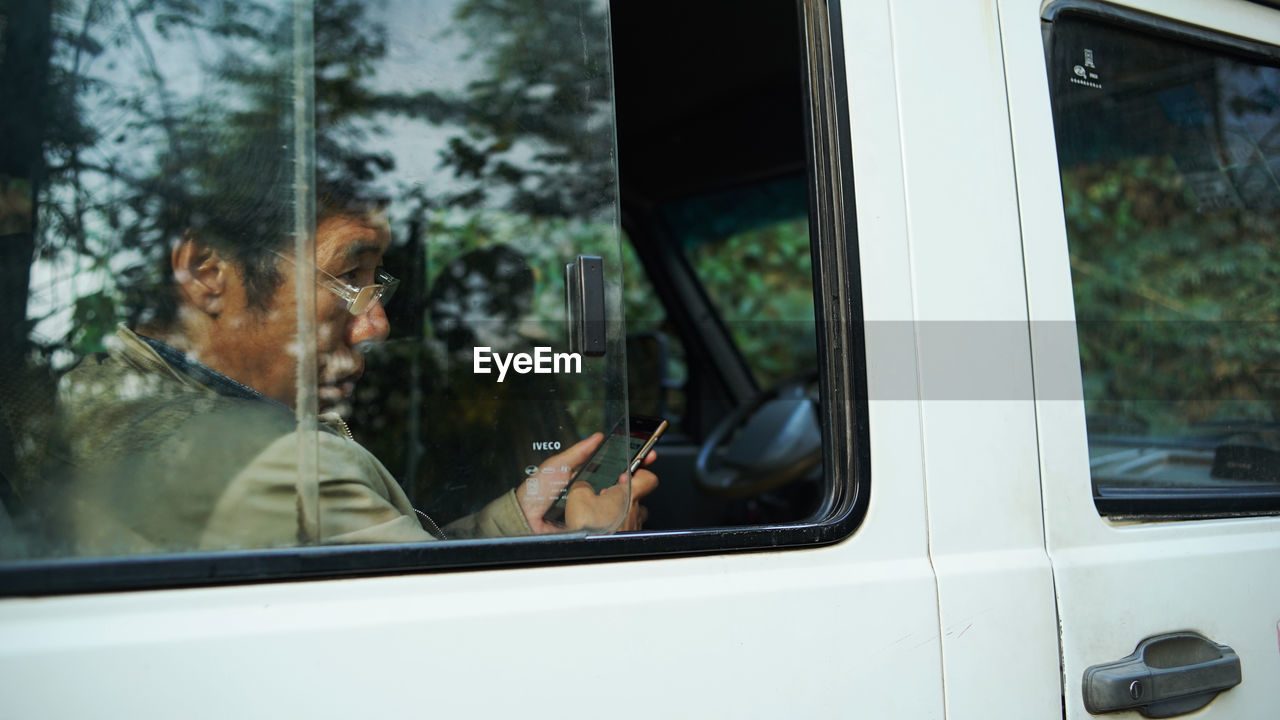 glass - material, window, transportation, real people, car, mode of transport, land vehicle, one person, looking through window, windshield, day, headshot, men, close-up, tree, outdoors, human hand, mammal, people