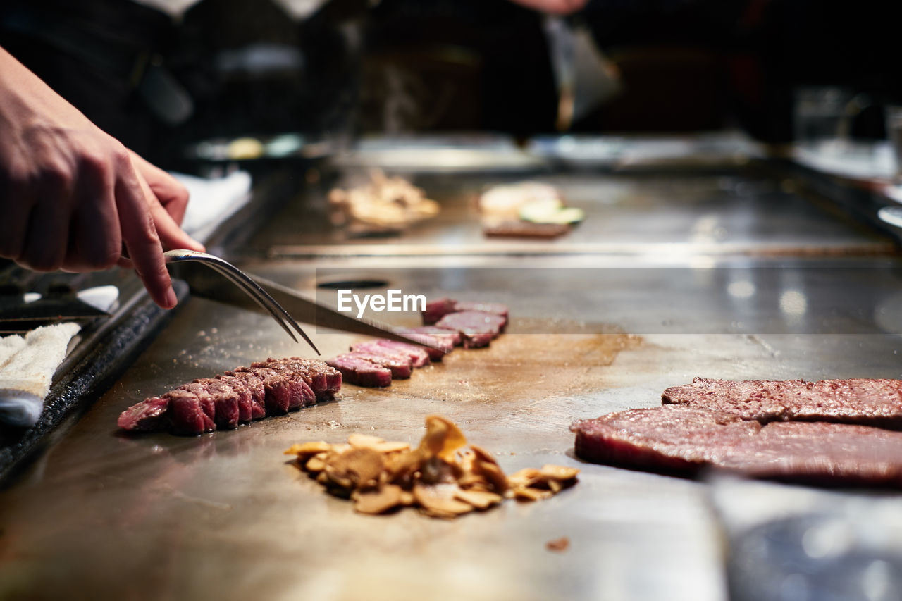 human hand, hand, food and drink, food, one person, preparation, human body part, freshness, preparing food, real people, unrecognizable person, indoors, selective focus, raw food, meat, chef, cutting, close-up, holding, finger, tray