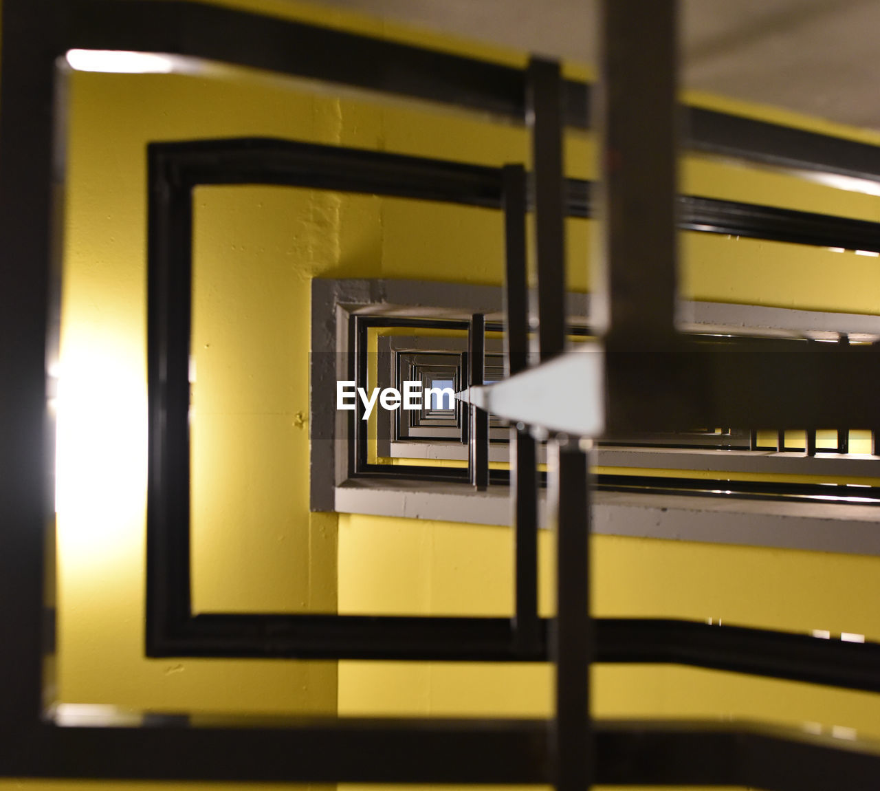 yellow, architecture, no people, indoors, built structure, metal, selective focus, sunlight, illuminated, railing, communication, wall - building feature, sign, day, close-up, lighting equipment, focus on background, public transportation, pattern