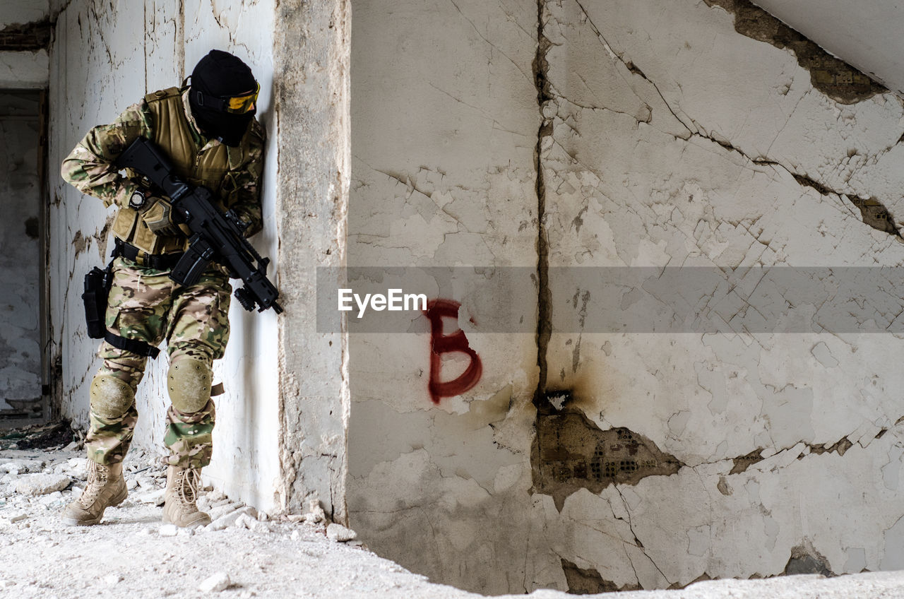 Man Holding Rifle While Standing Against Wall