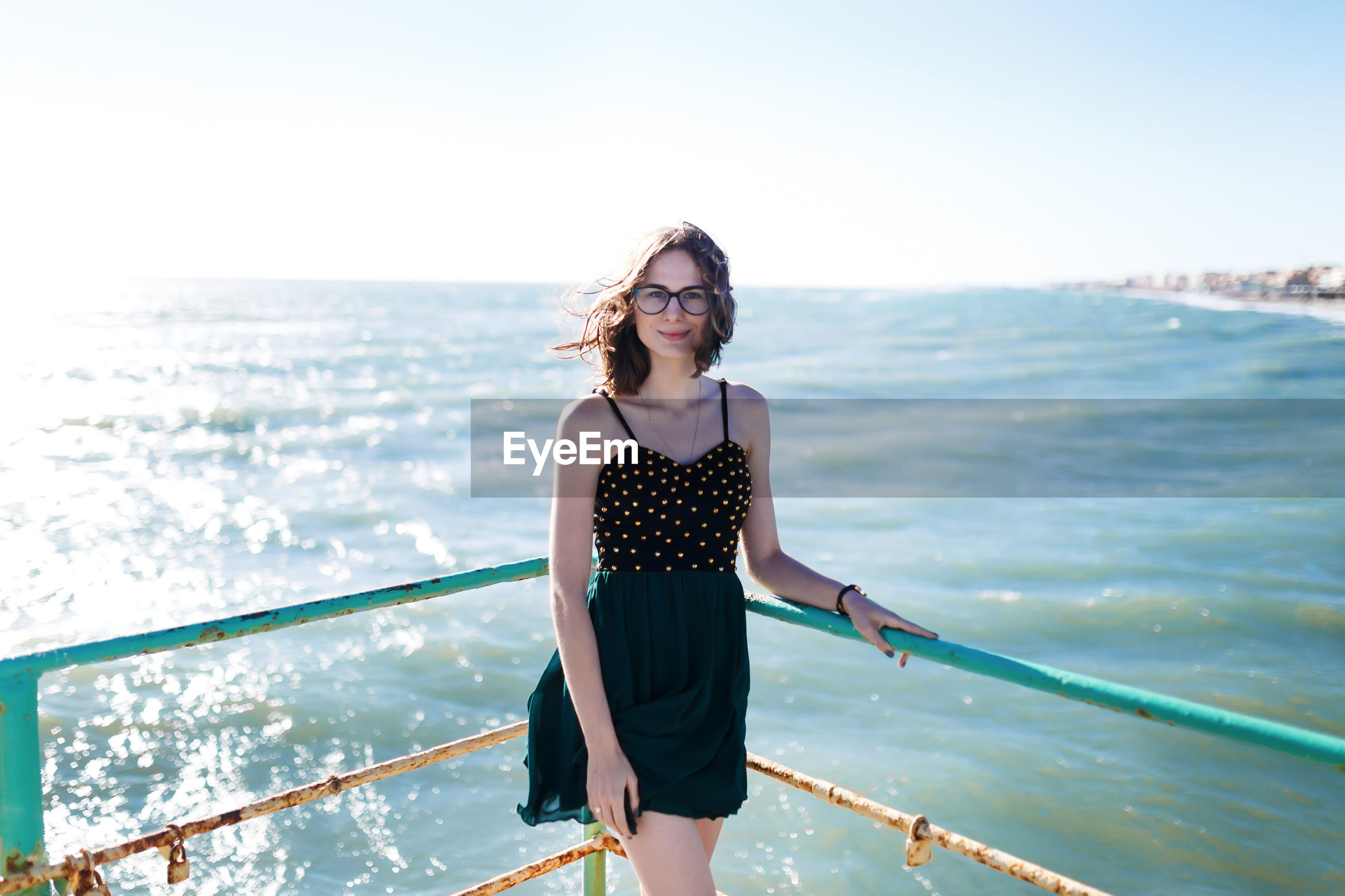FULL LENGTH OF YOUNG WOMAN STANDING AT SEA AGAINST SKY