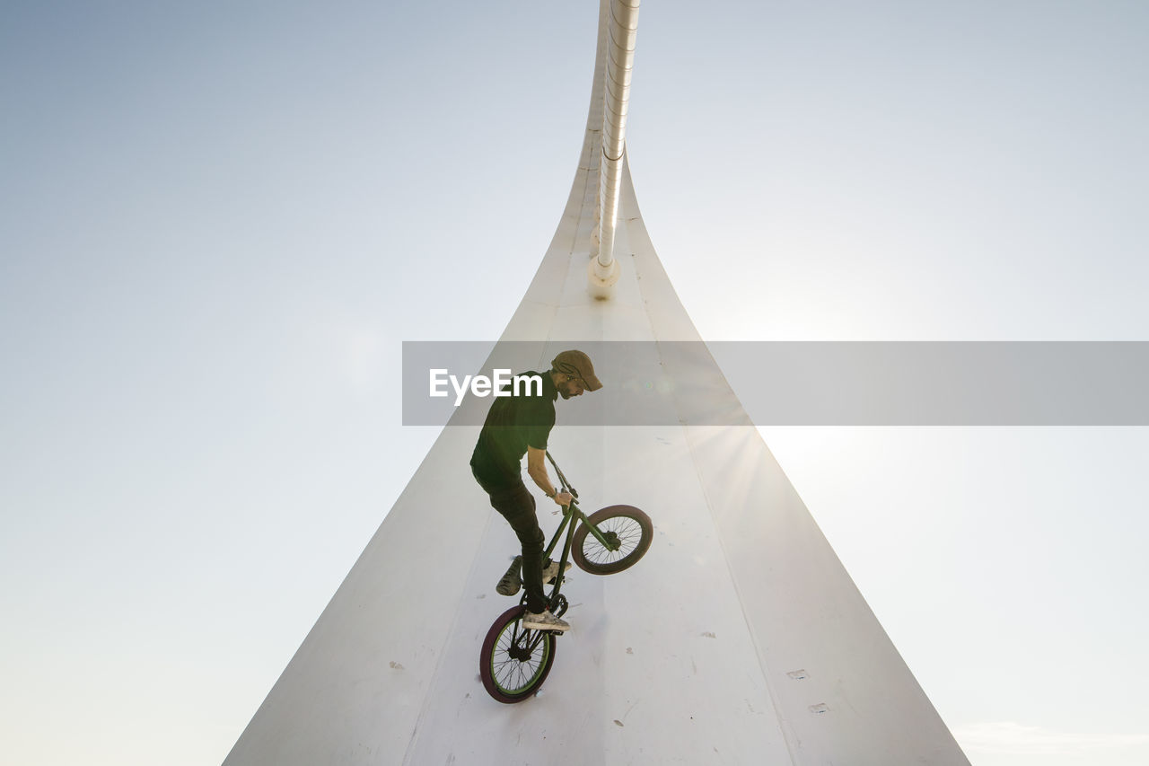 sky, sport, low angle view, leisure activity, day, lifestyles, real people, extreme sports, one person, nature, men, clear sky, full length, copy space, outdoors, adventure, sunlight, built structure, risk