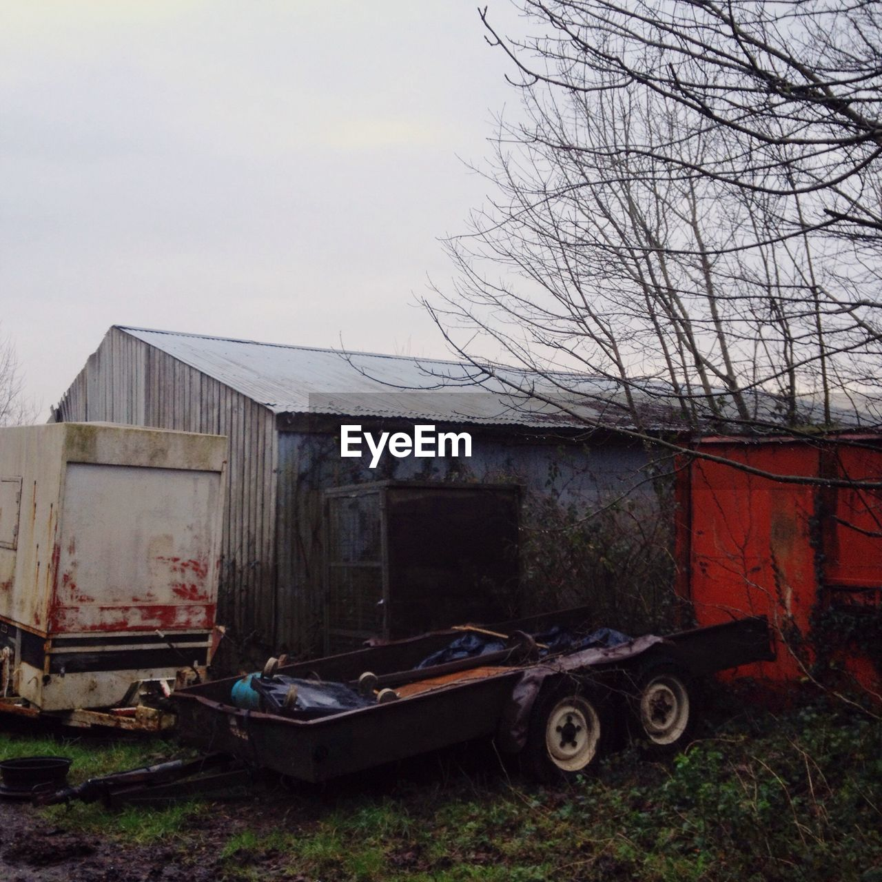 Abandoned Trailer By Barn On Field Against Sky
