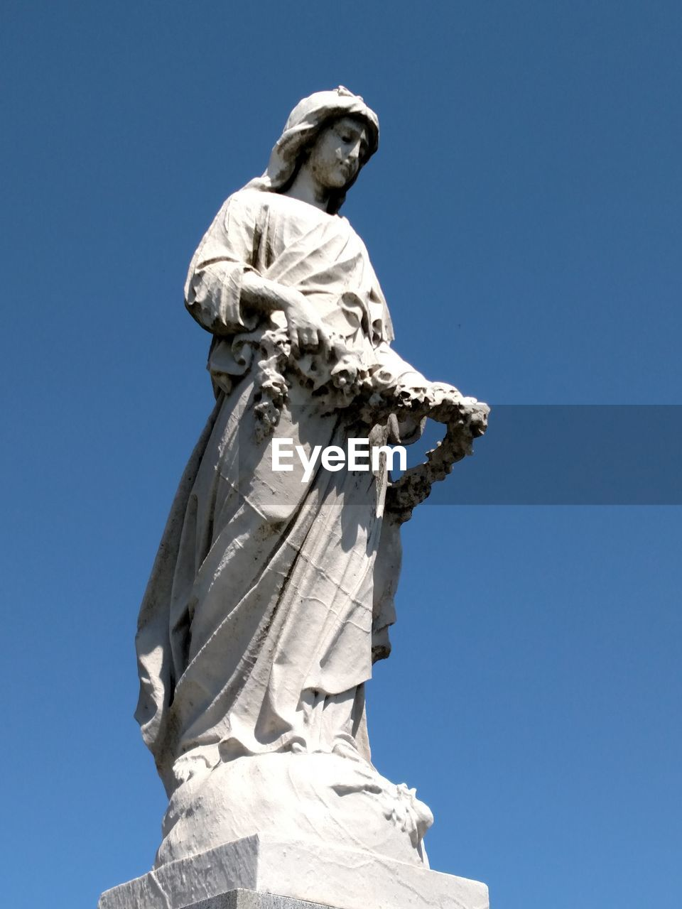 statue, sculpture, human representation, art and craft, low angle view, female likeness, male likeness, creativity, craft, clear sky, travel destinations, travel, outdoors, day, no people, blue, sky