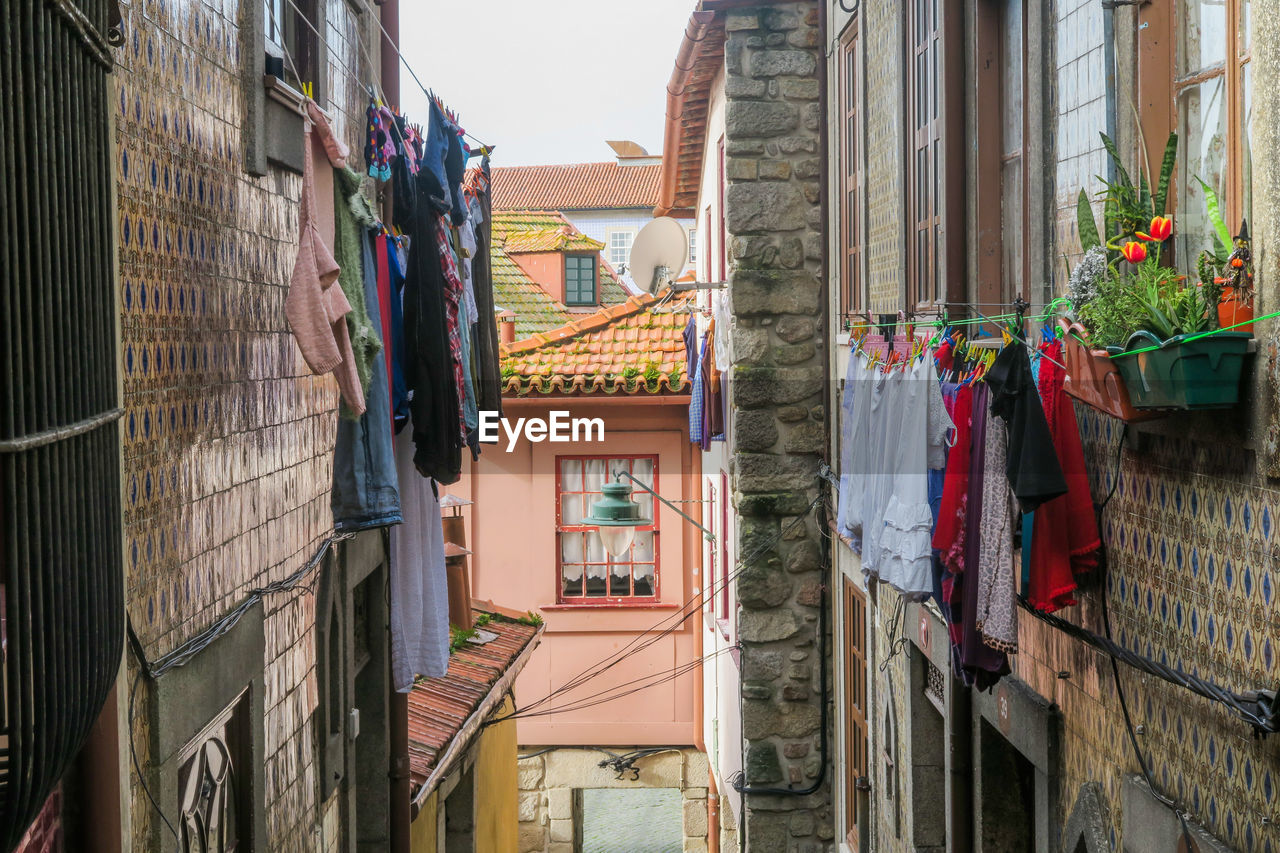 building exterior, architecture, built structure, building, residential district, hanging, day, house, no people, window, drying, city, low angle view, nature, clothing, laundry, outdoors, textile, clothesline, roof, alley