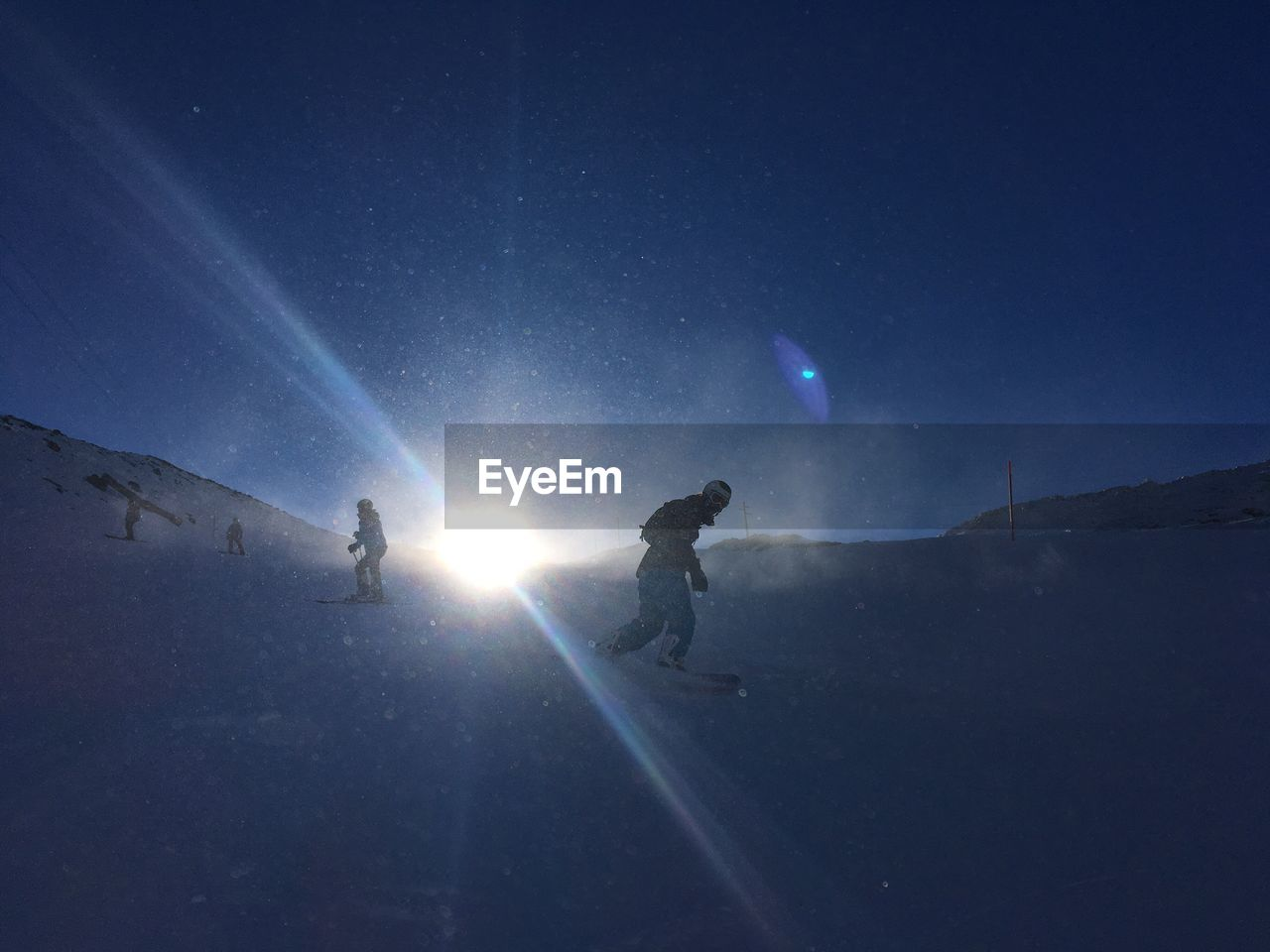 real people, lens flare, leisure activity, sun, adventure, men, two people, sunlight, sky, full length, outdoors, nature, low angle view, moon, extreme sports, winter, blue, lifestyles, moonlight, flashlight, star - space, togetherness, beauty in nature, astronomy, snowboarding, people