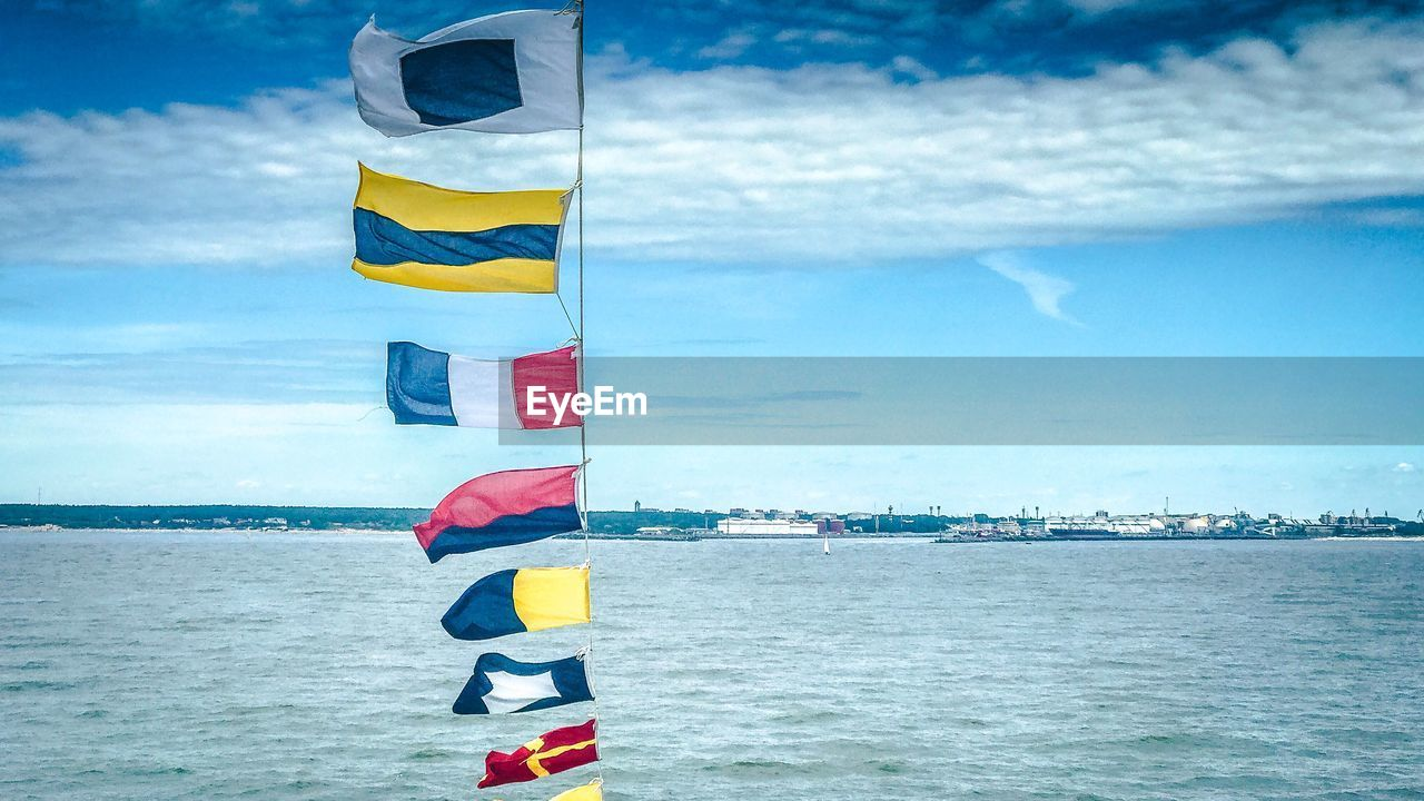 sky, flag, water, cloud - sky, patriotism, sea, nature, no people, pole, day, pride, beauty in nature, scenics - nature, yellow, wind, environment, multi colored, outdoors, national icon, independence