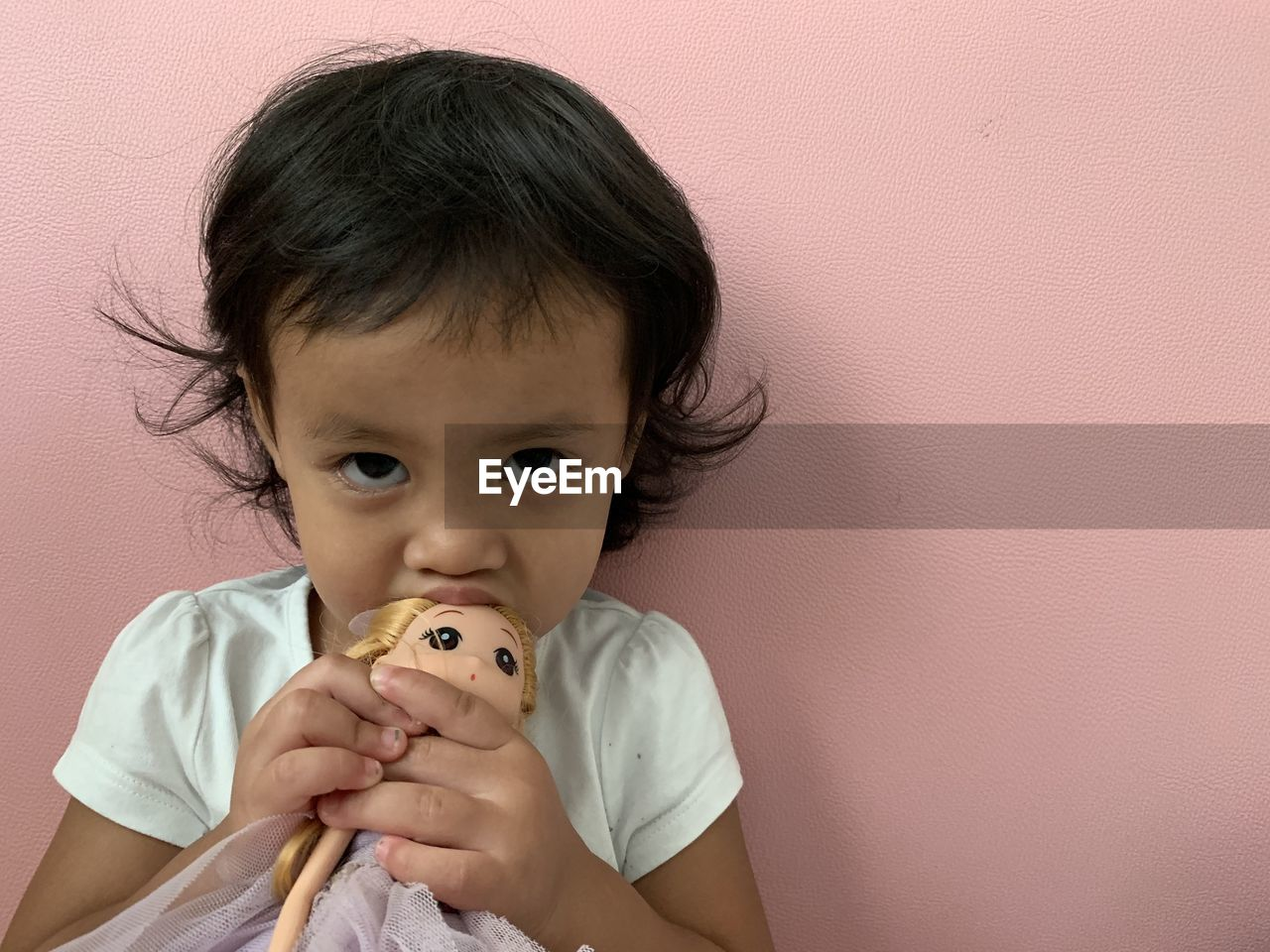 Portrait of cute girl biting toy against wall