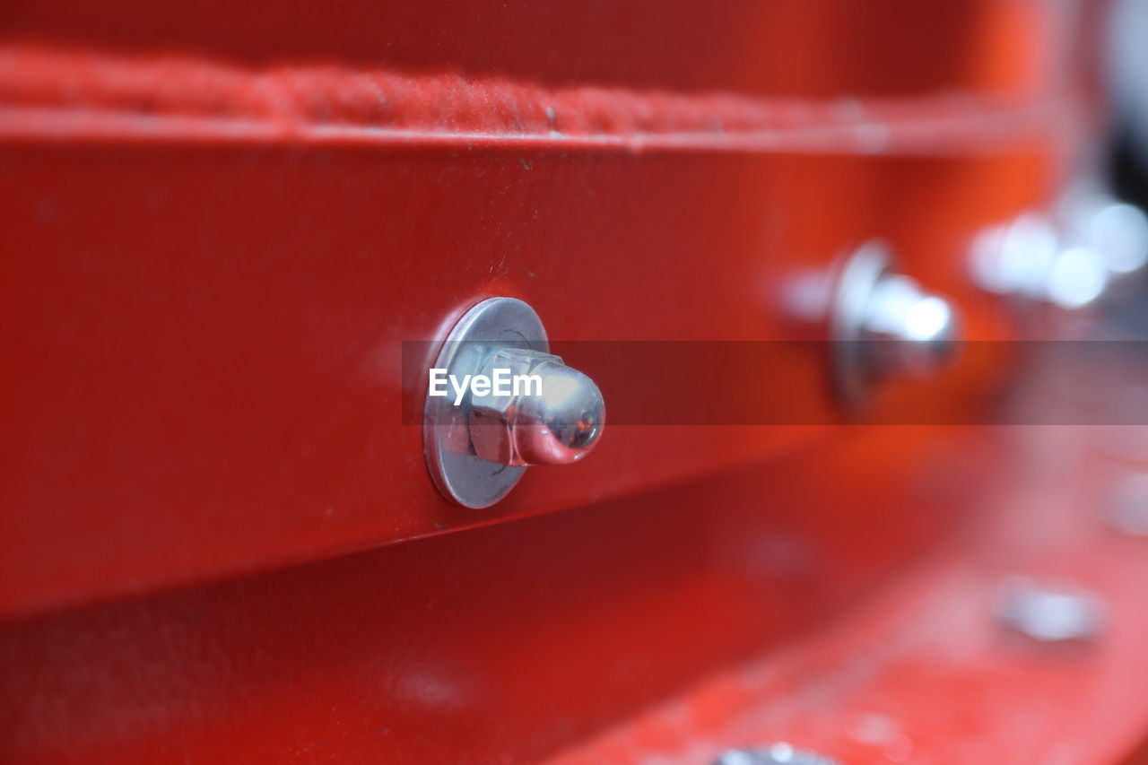 Close-Up Of Nut And Bolt On Red Metal
