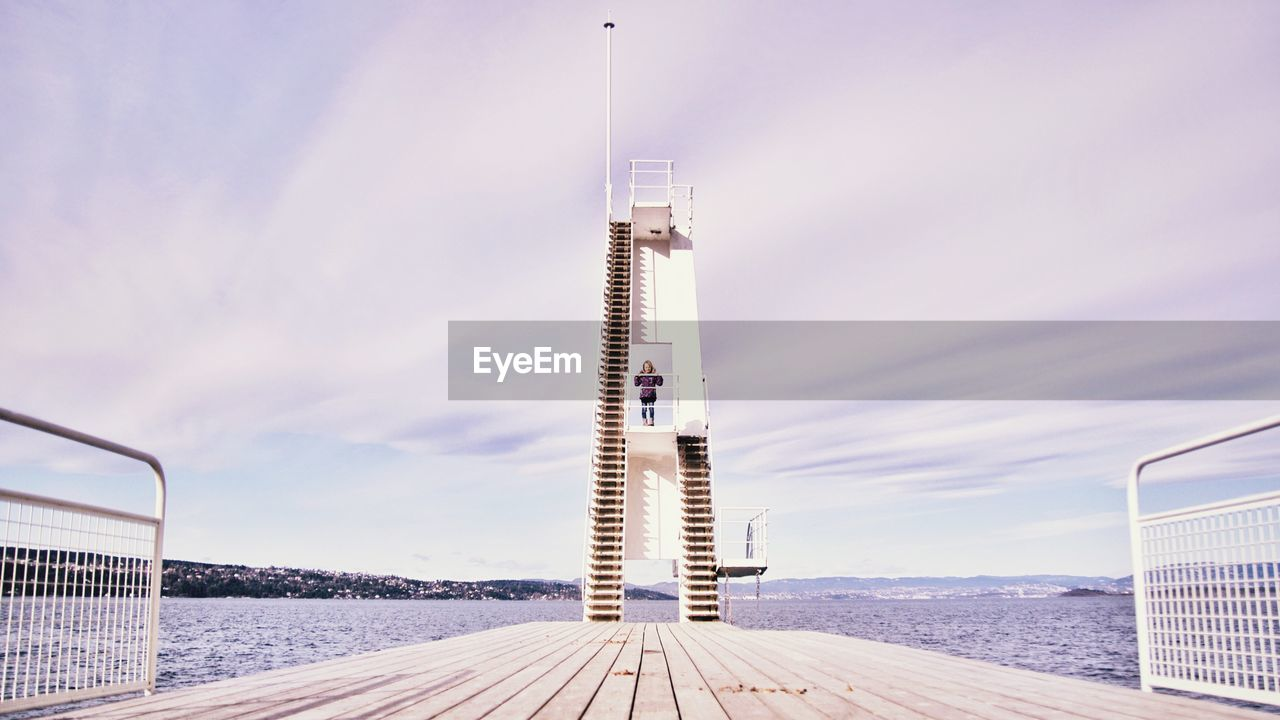 Woman standing on diving platform by river against sky