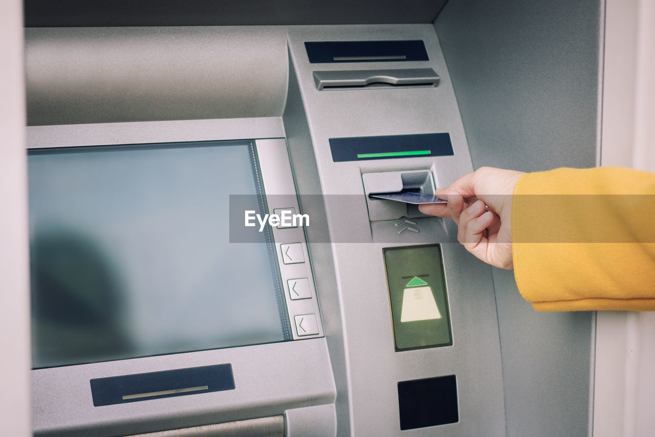Cropped hand of woman inserting card in atm machine