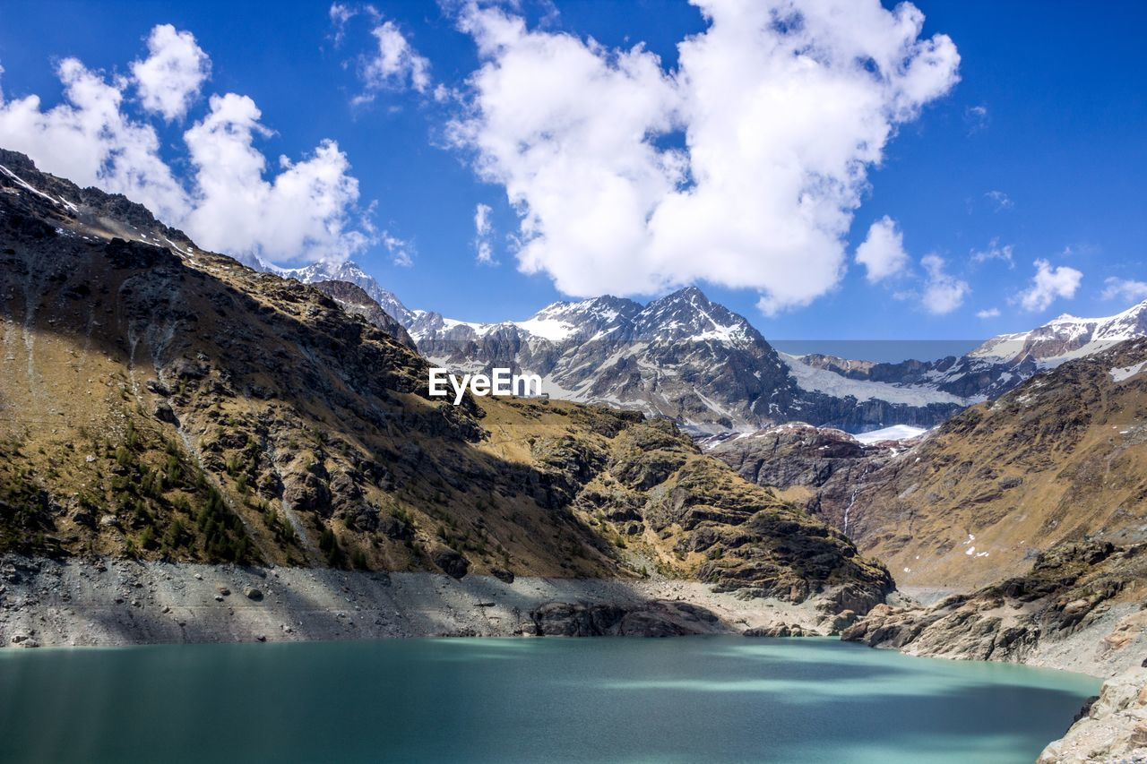 mountain, scenics, beauty in nature, tranquil scene, sky, nature, tranquility, cloud - sky, water, mountain range, lake, no people, outdoors, day, cold temperature, snow, iceberg
