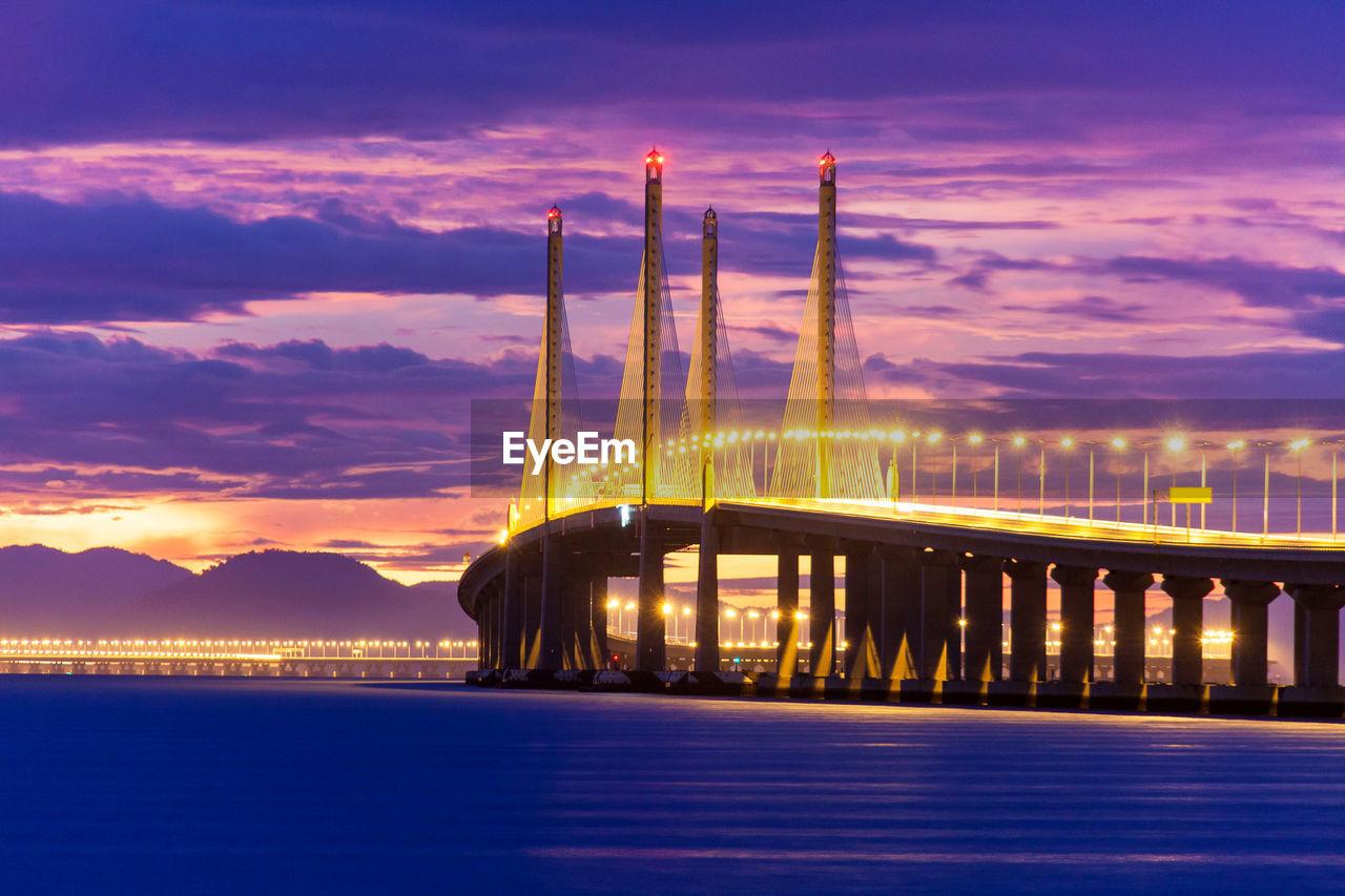Illuminated Bridge Over Sea Against Cloudy Sky At Dusk
