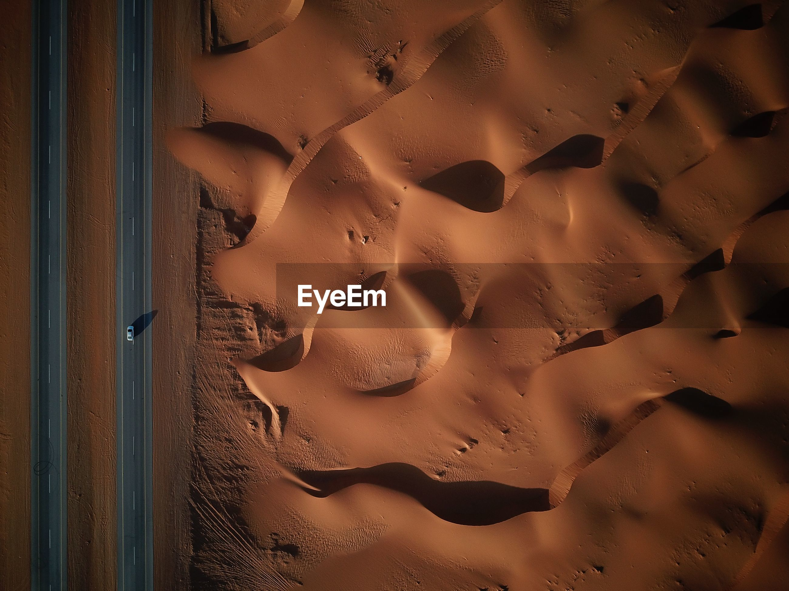 Aerial view of road by sand at desert