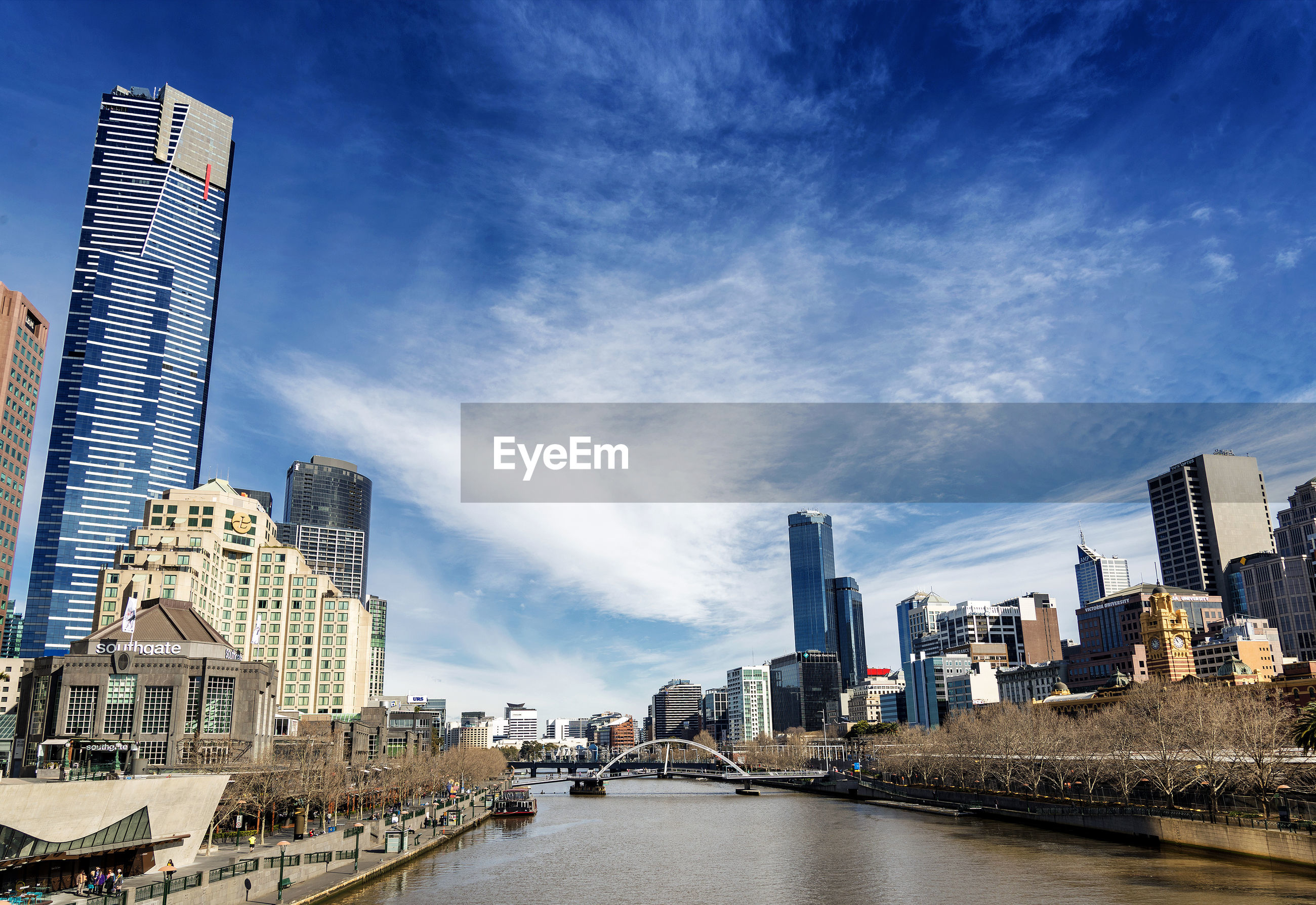 CITY BUILDINGS BY RIVER AGAINST SKY