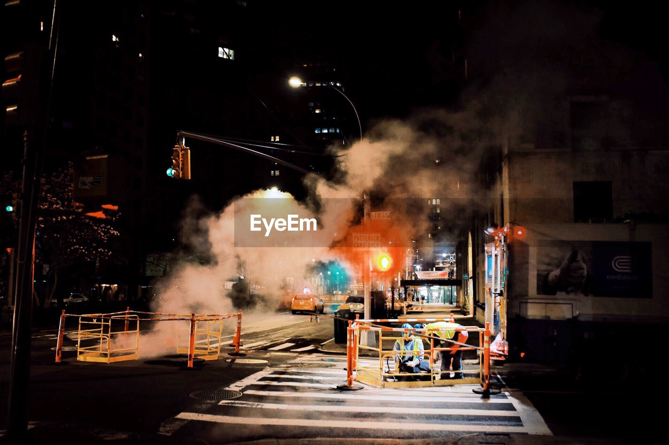 night, architecture, illuminated, building exterior, smoke - physical structure, transportation, city, street, mode of transportation, built structure, sign, no people, outdoors, motion, nature, land vehicle, road, motor vehicle, car, industry, pollution, air pollution