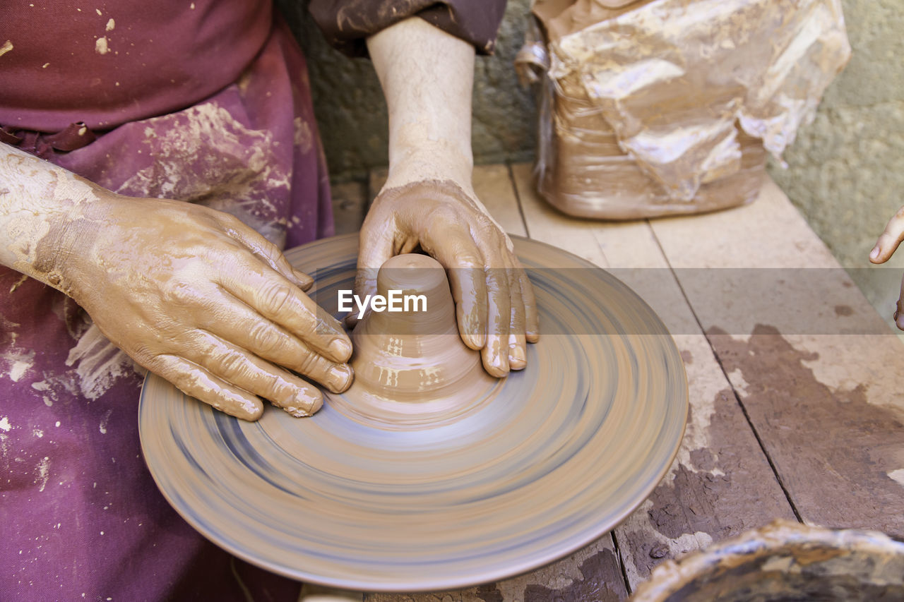craft, working, art and craft, spinning, pottery, human hand, clay, molding a shape, creativity, skill, one person, occupation, hand, real people, making, expertise, human body part, preparation, dirt, craftsperson, mud, outdoors, finger