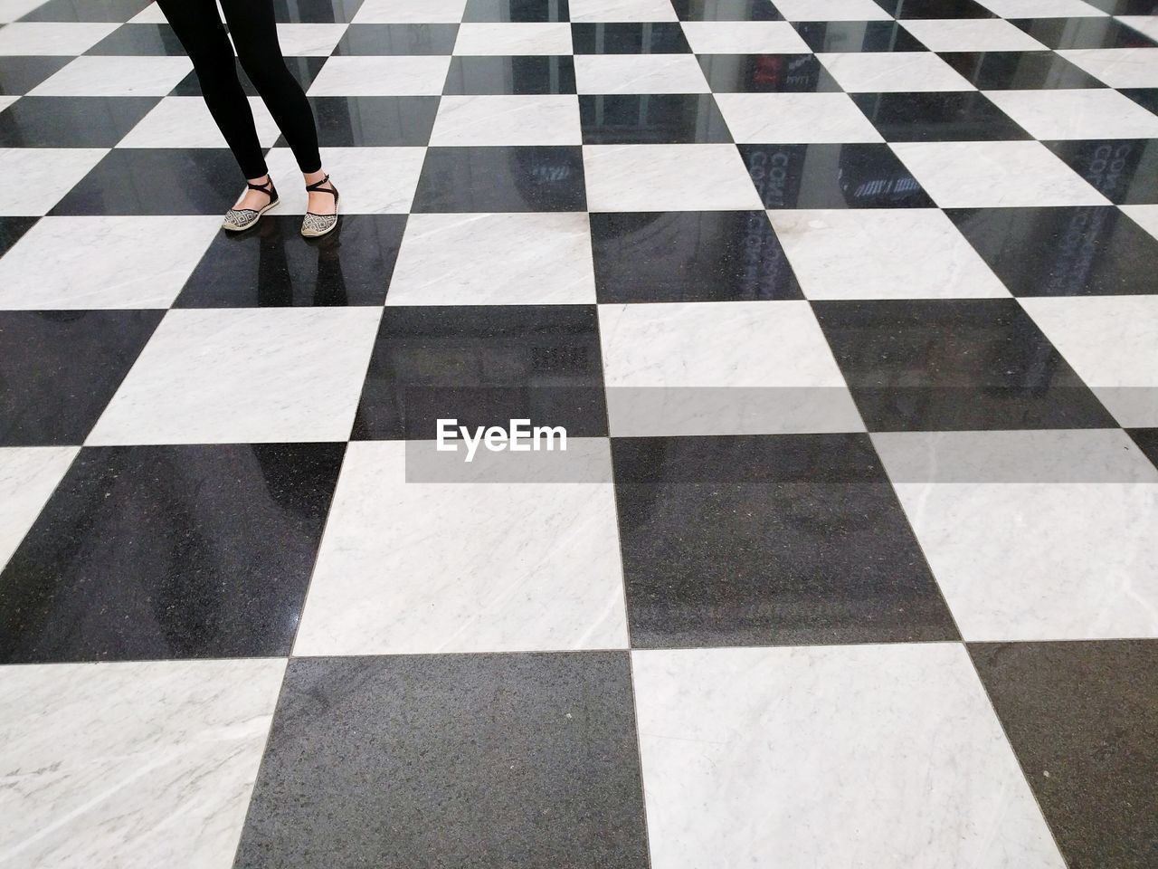 Low Section Of Woman Standing On Checked Pattern Floor