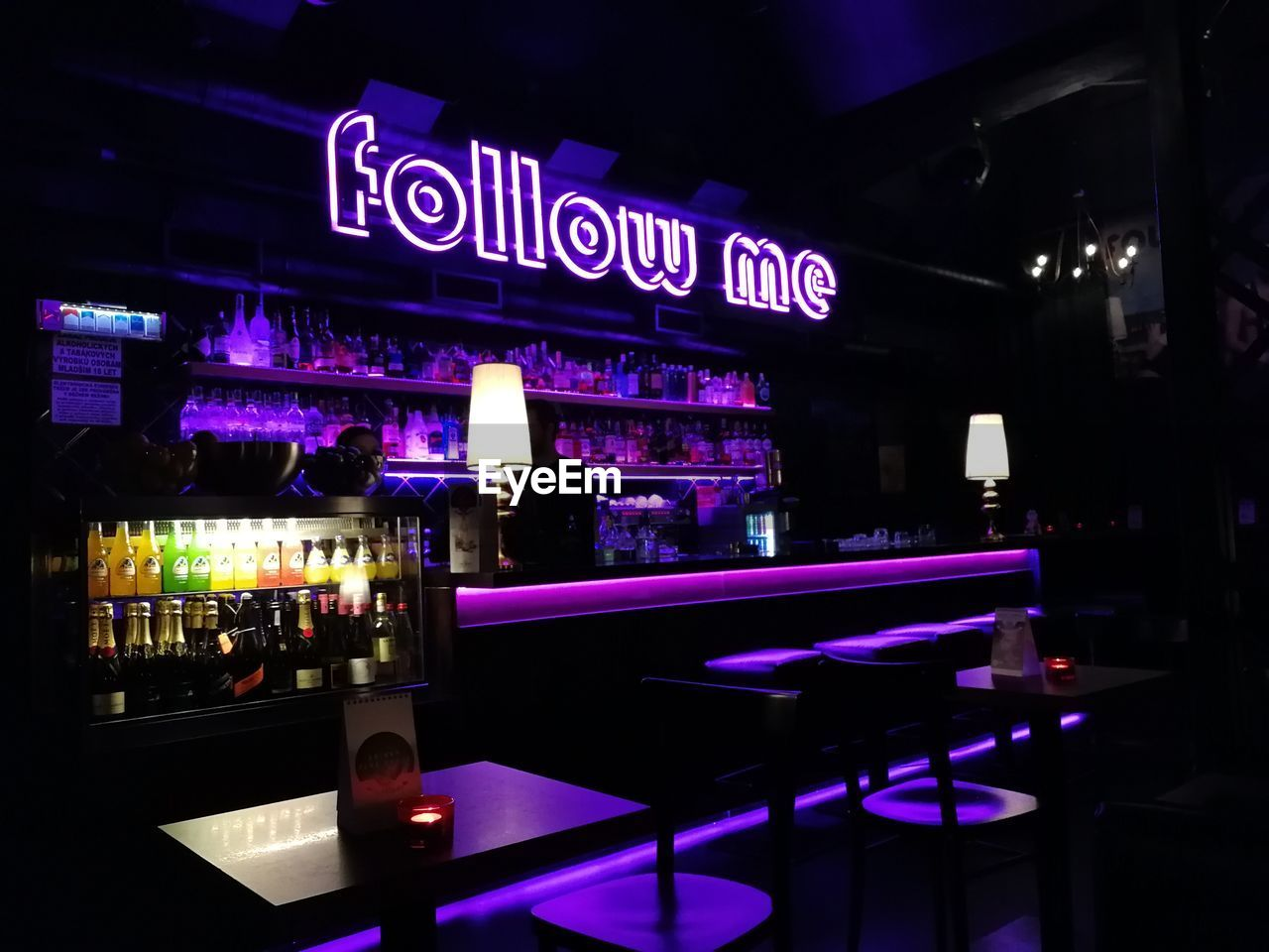 illuminated, bar - drink establishment, night, text, western script, food and drink, restaurant, bar counter, drink, table, communication, indoors, nightclub, refreshment, business, no people, architecture, built structure, neon, nightlife, purple