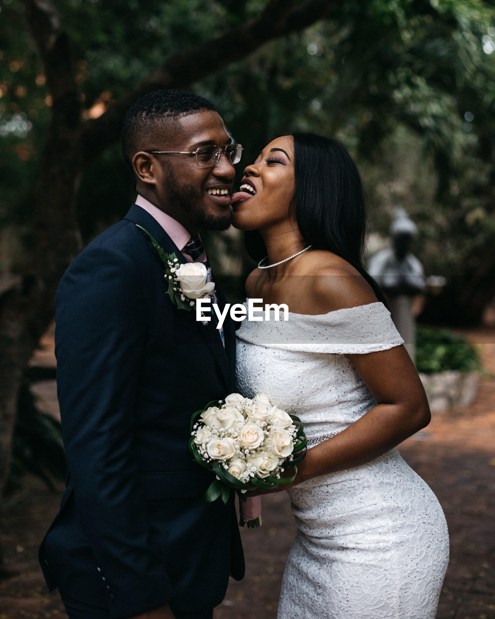 Bride licking groom cheek against trees