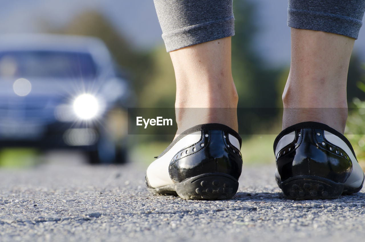 Low Section Of Woman Standing On Road With Car In Background
