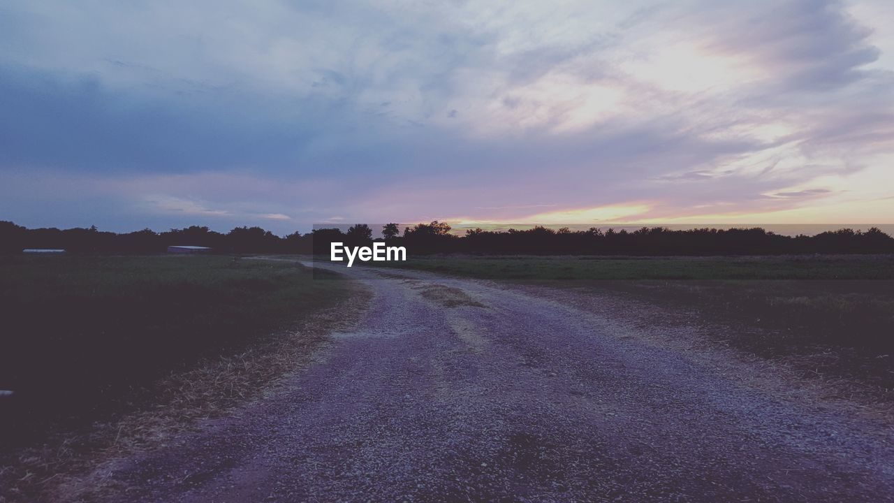 sunset, tranquil scene, landscape, scenics, nature, tranquility, sky, no people, cloud - sky, beauty in nature, road, field, outdoors, the way forward, rural scene, day, grass