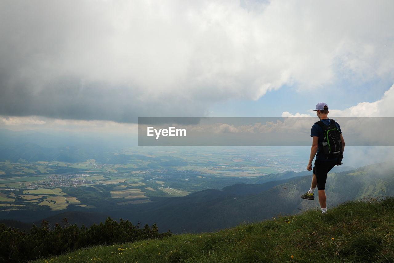 FULL LENGTH OF MAN STANDING ON MOUNTAIN