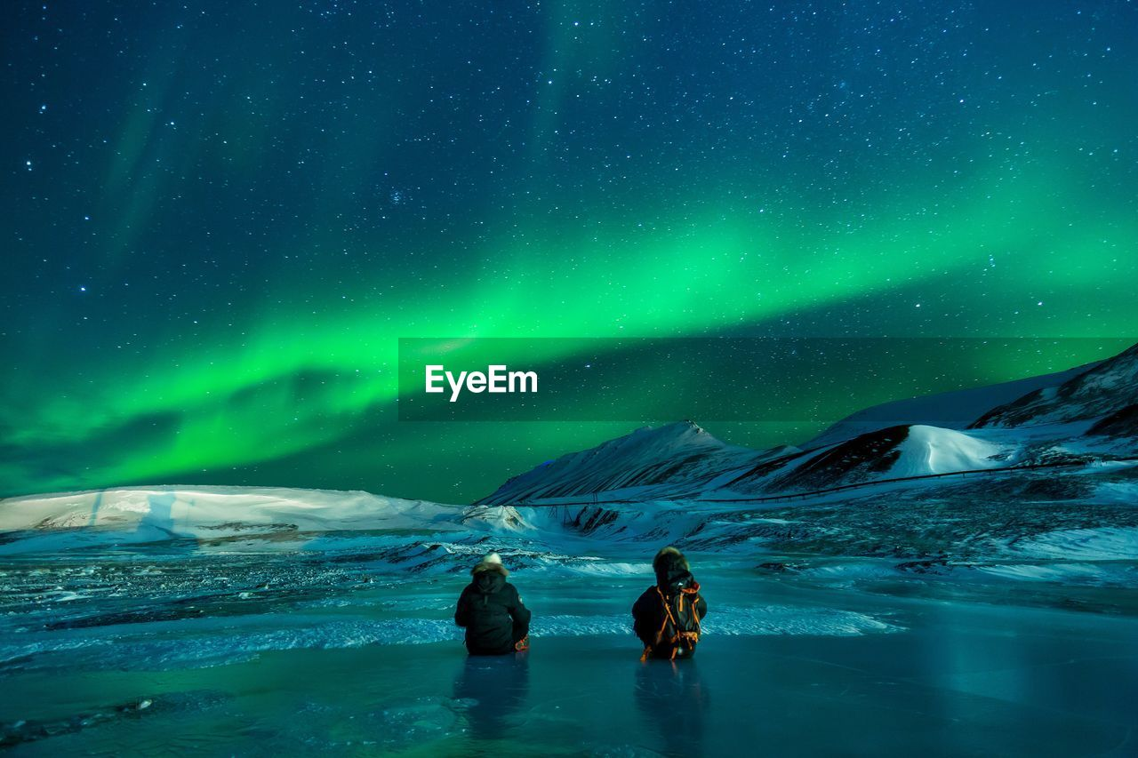 People On Snow Covered Field Looking At Aurora Polaris