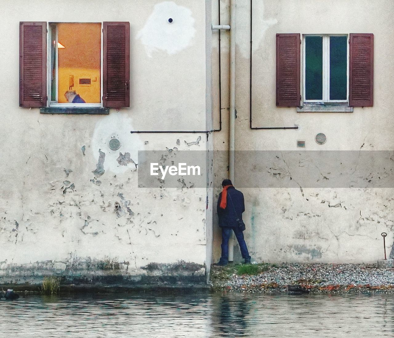 architecture, built structure, real people, one person, building exterior, window, day, water, building, reflection, lifestyles, wall - building feature, men, full length, standing, outdoors, wet, city