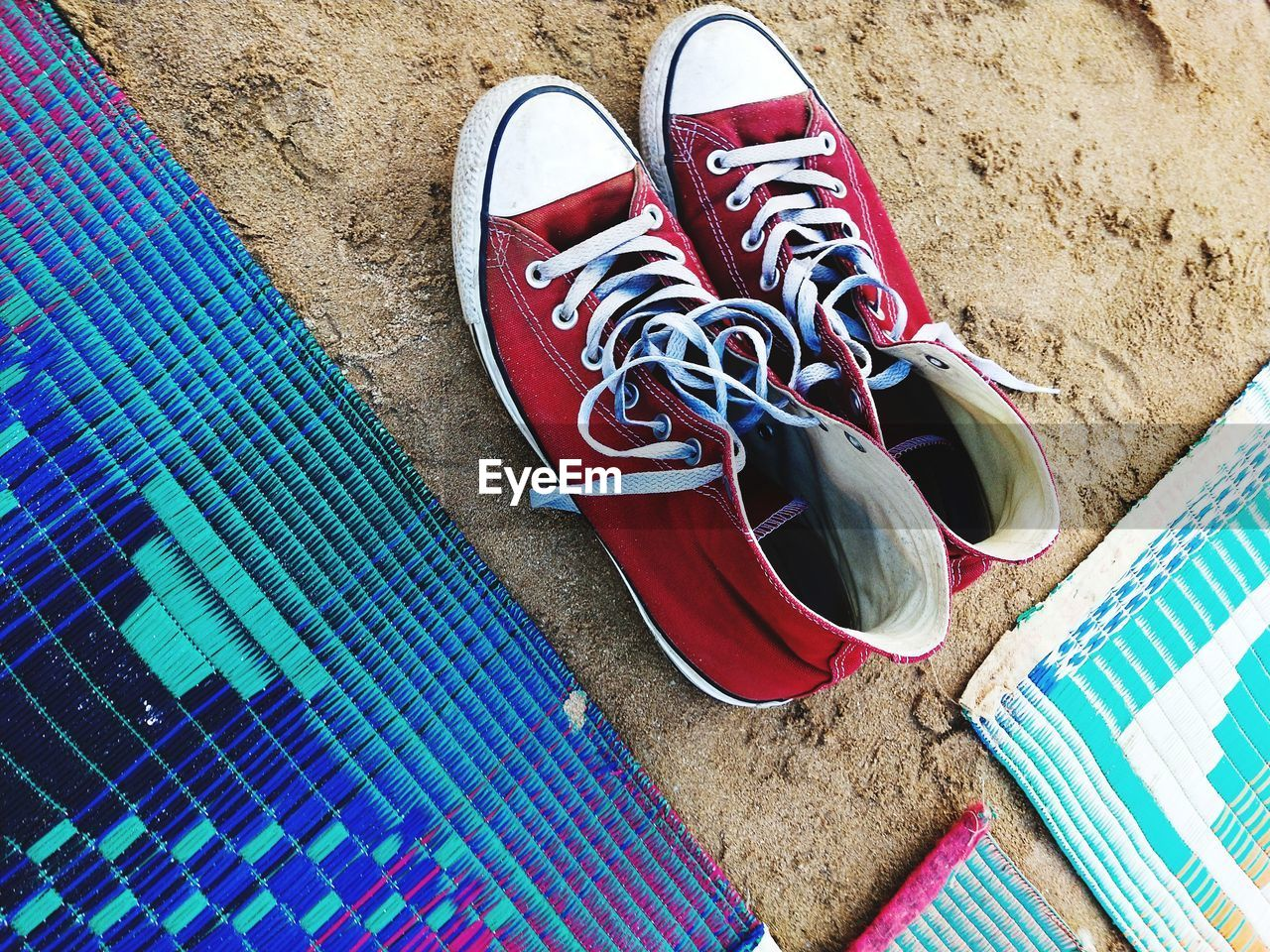 HIGH ANGLE VIEW OF SHOES ON THE SAND