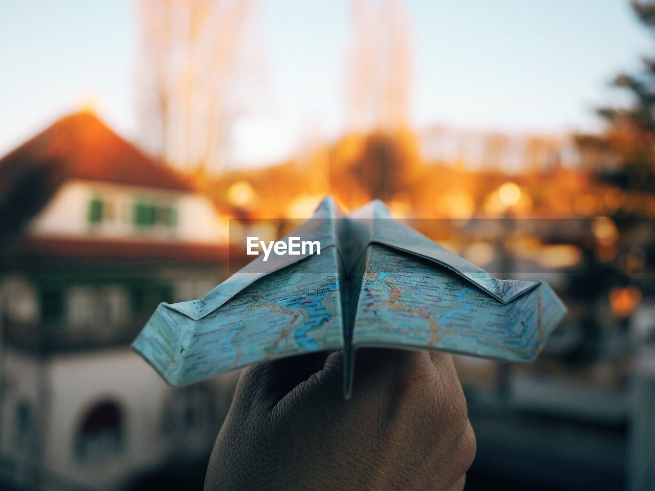 Cropped image of hand holding paper airplane made of map against houses