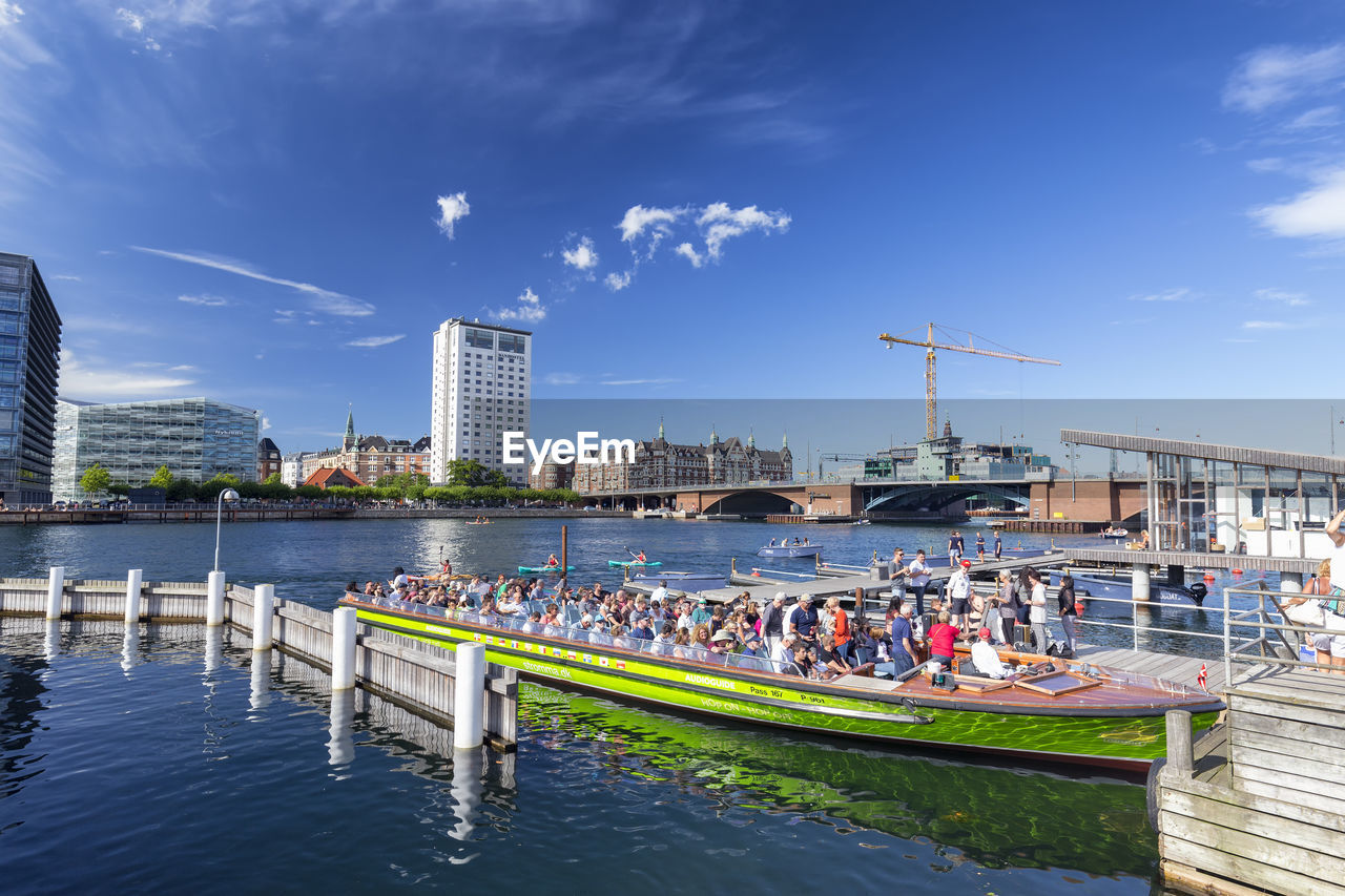 water, architecture, built structure, sky, building exterior, waterfront, nature, river, cloud - sky, nautical vessel, day, group of people, real people, transportation, city, crowd, large group of people, building, crane - construction machinery, outdoors, office building exterior, skyscraper