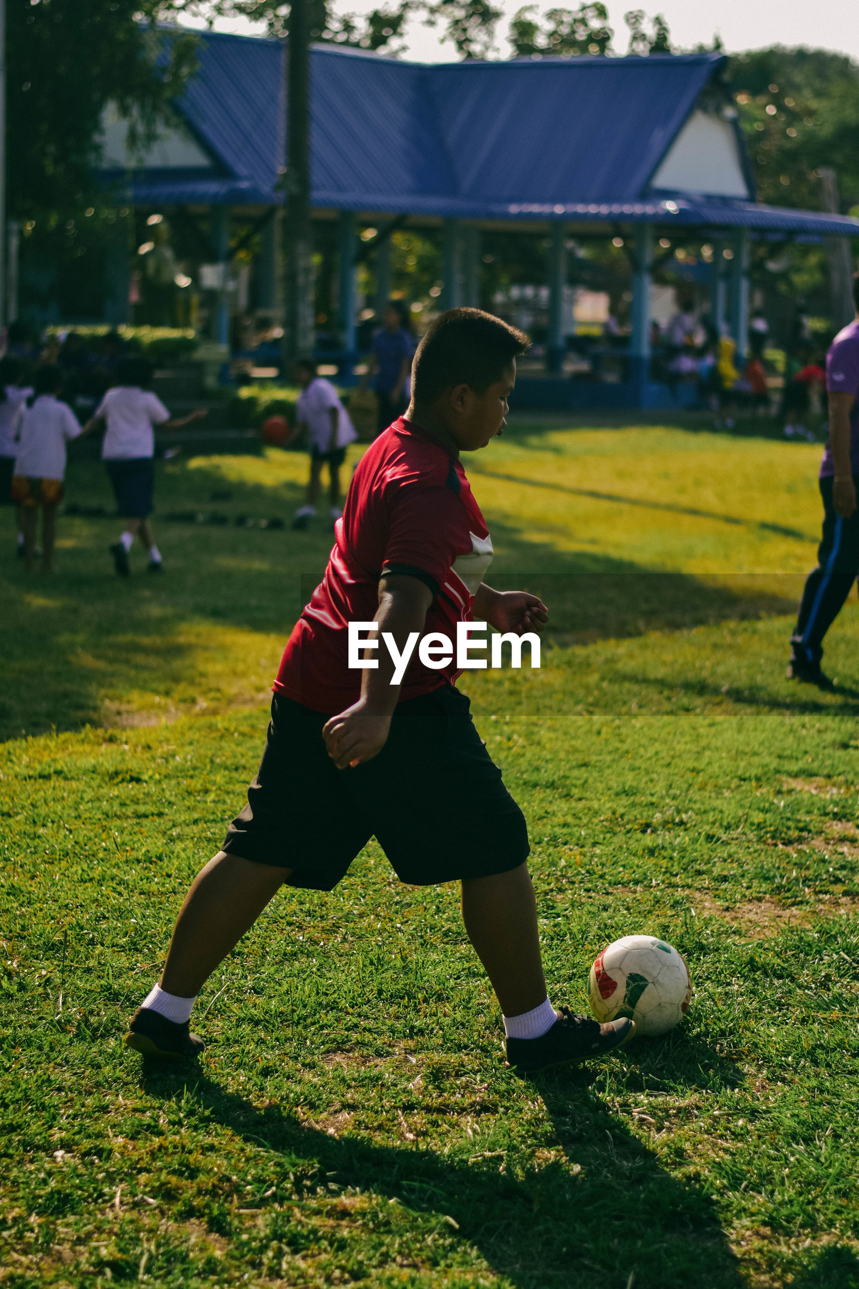 Side view of boy playing soccer on field
