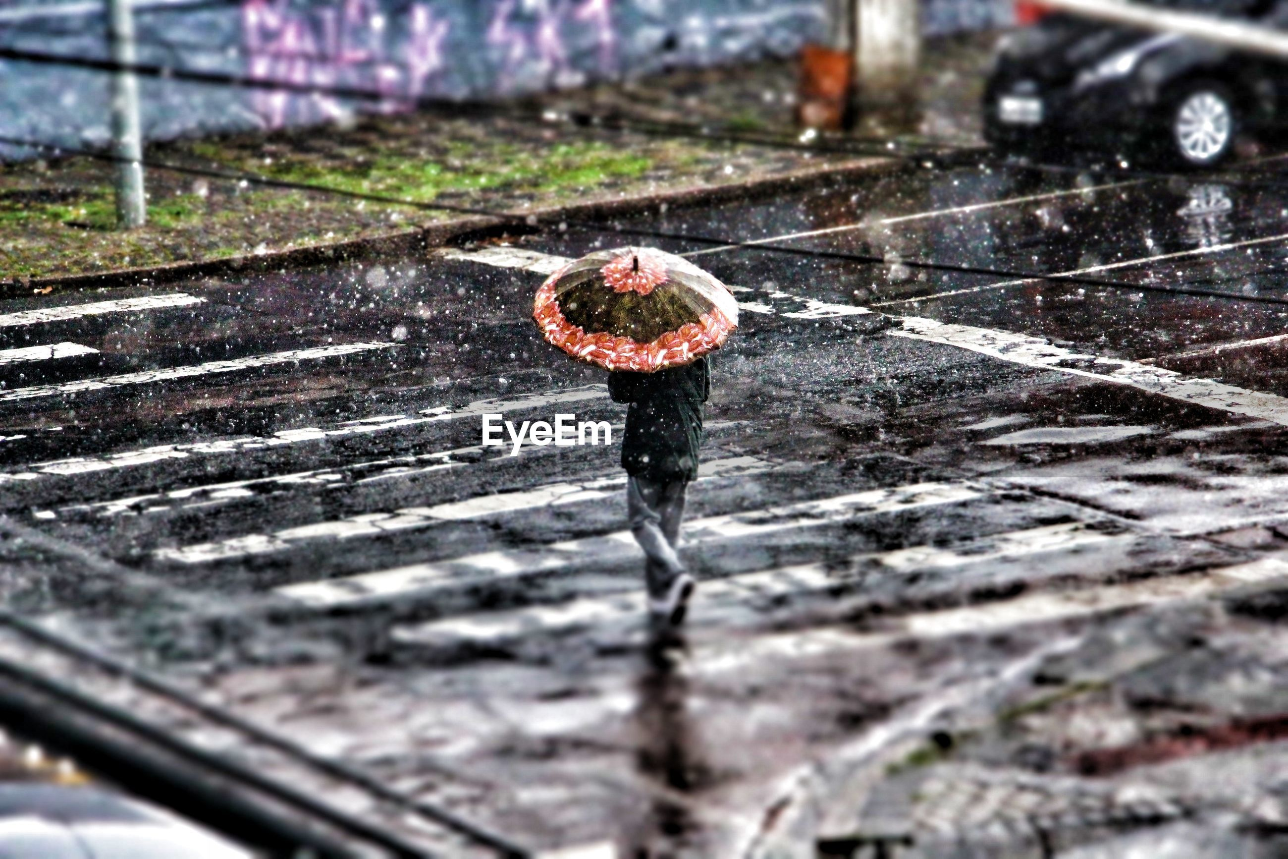 Person with umbrella crossing road during rainfall