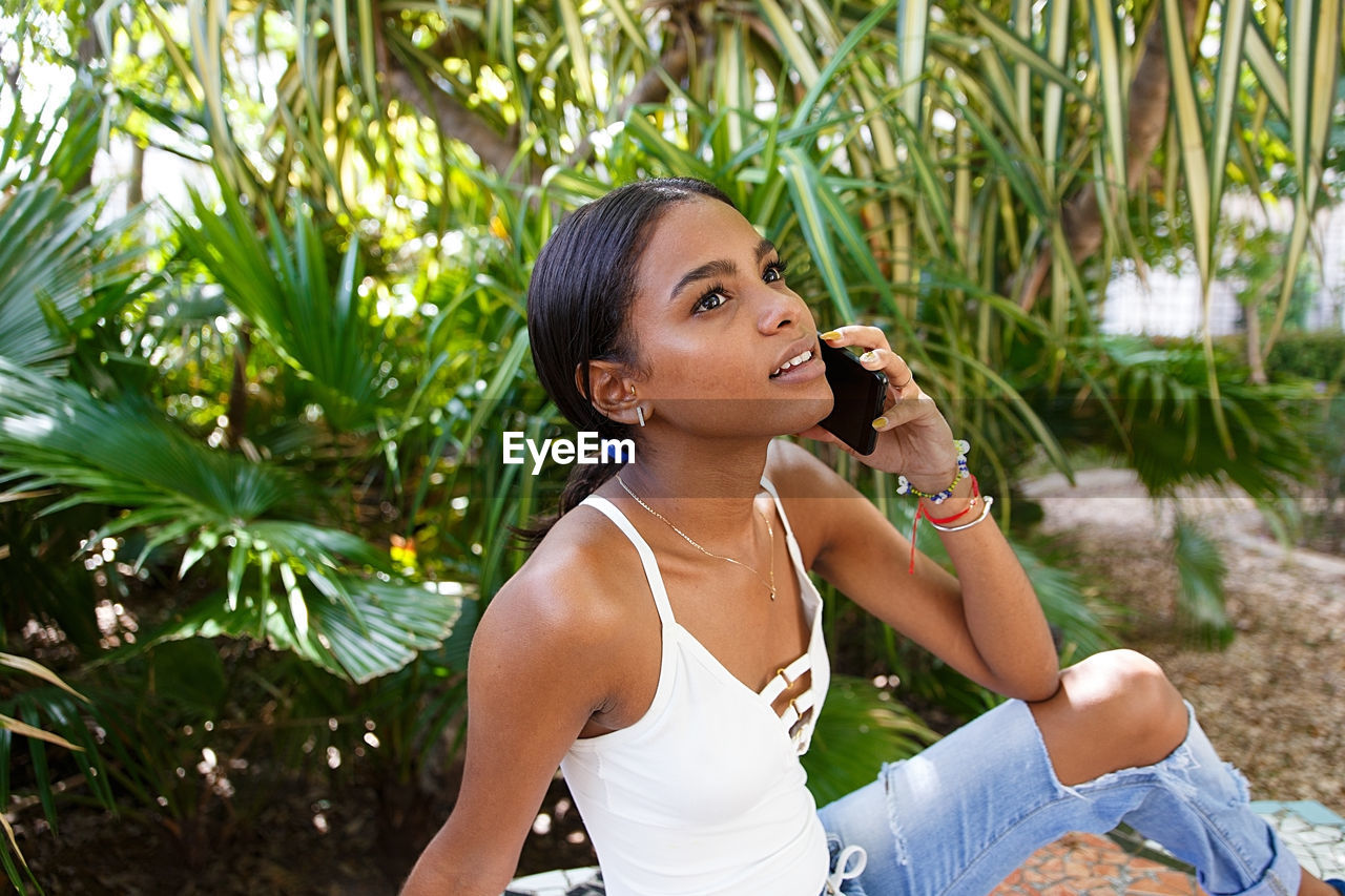 Smiling young woman listening over phone while sitting by plants