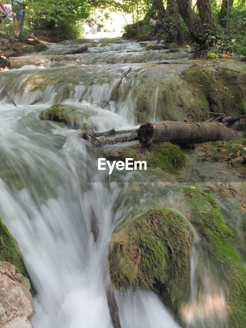 Low Angle View Of Water Flowing Over Rocks At Field