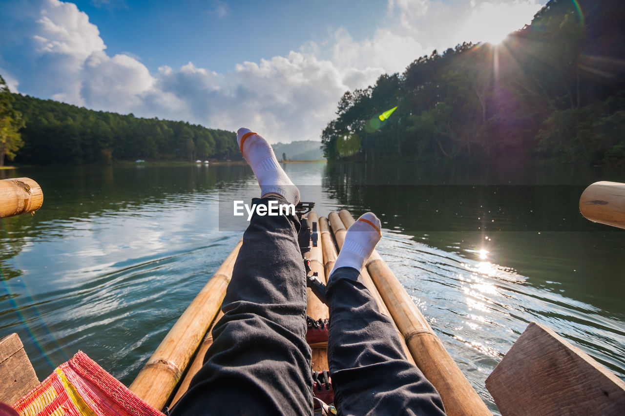 Low section of person relaxing on wooden raft in lake