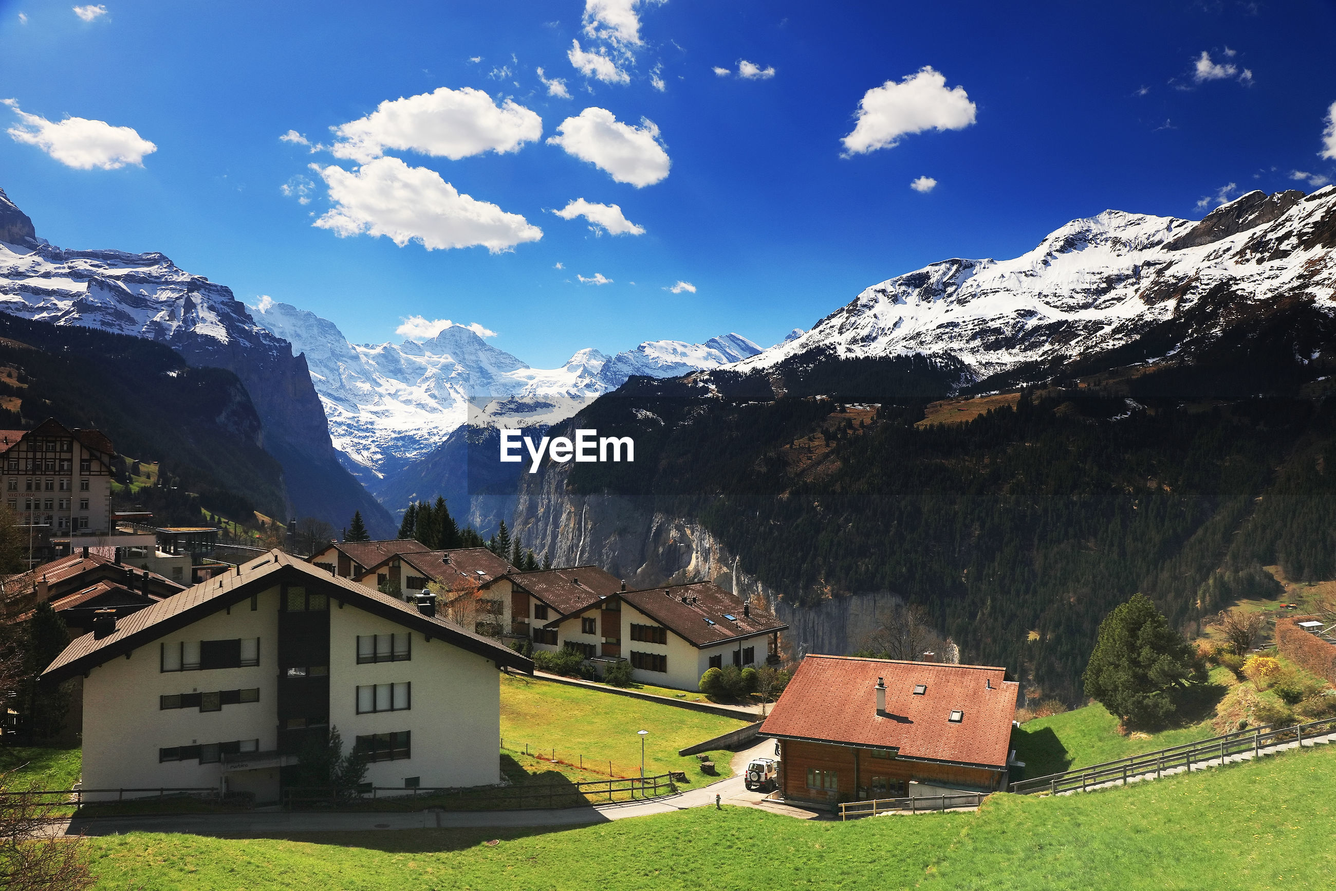 HOUSES ON FIELD AGAINST MOUNTAINS