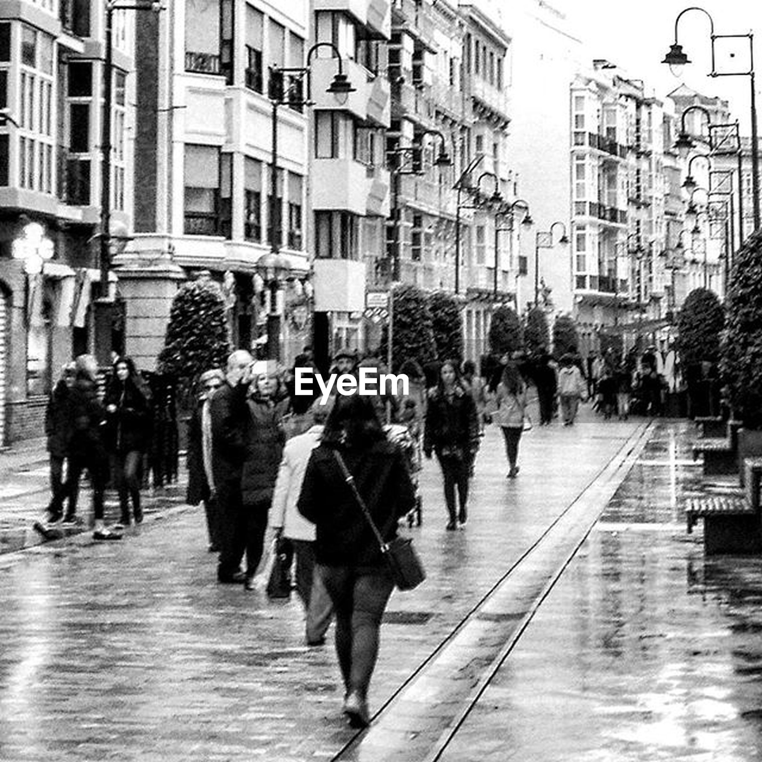 large group of people, building exterior, architecture, built structure, person, city, walking, men, street, city life, lifestyles, leisure activity, mixed age range, crowd, building, umbrella, the way forward, city street, day