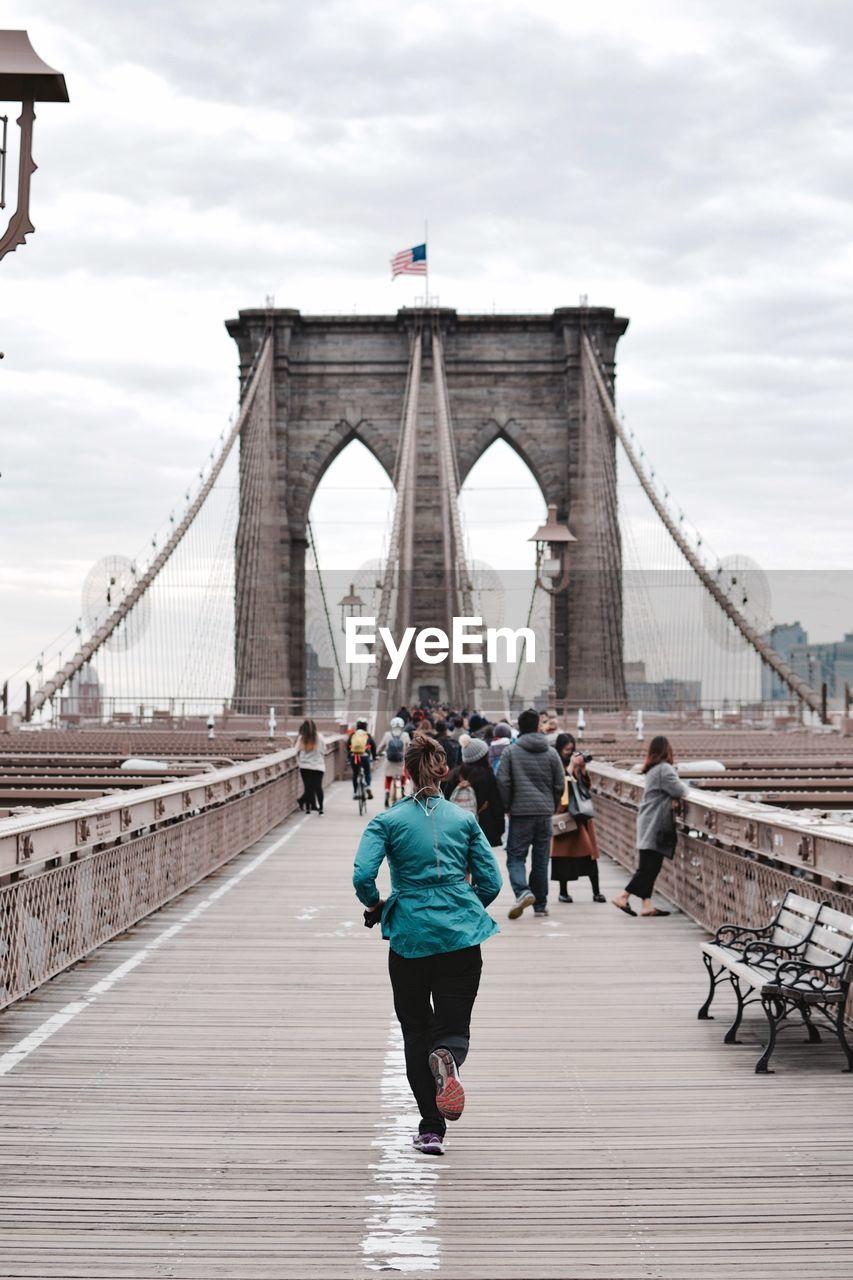 Rear View Of Woman Jogging On Brooklyn Bridge