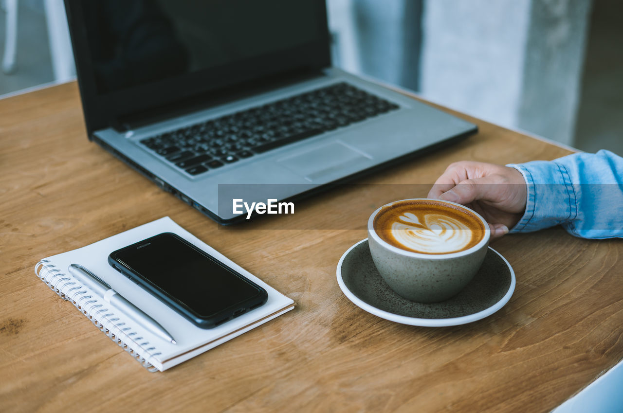 HIGH ANGLE VIEW OF COFFEE CUP ON LAPTOP