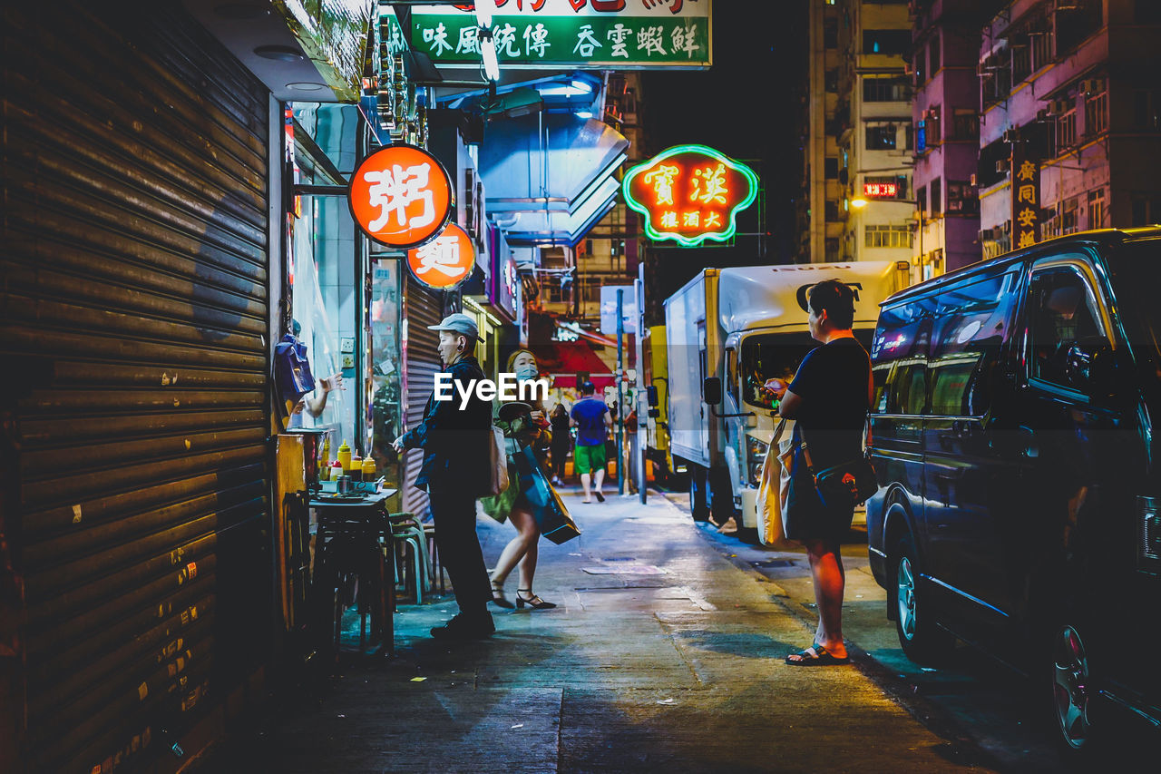 architecture, night, city, building exterior, built structure, illuminated, street, real people, sign, walking, lighting equipment, city life, transportation, lifestyles, communication, women, men, people, footpath, motion