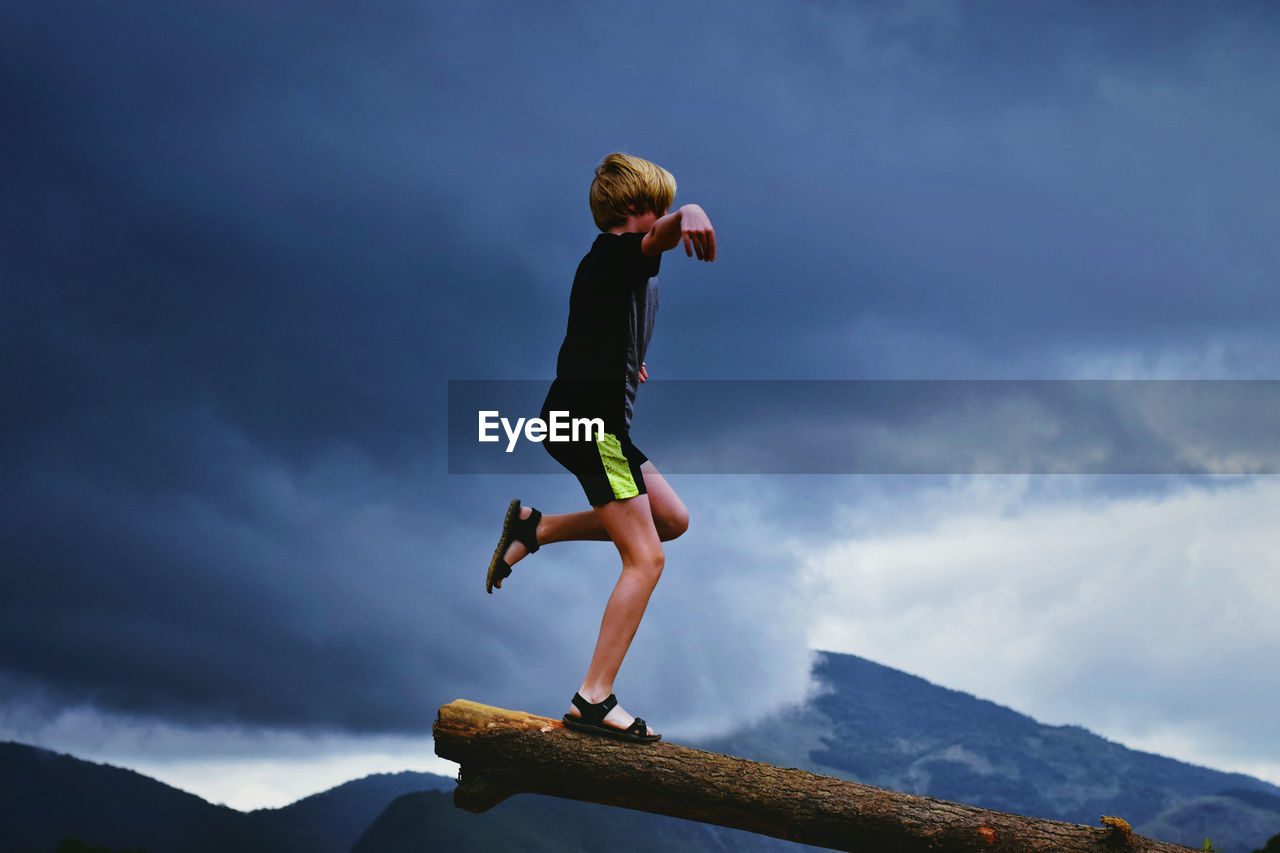 Side View Of Boy Standing On Log By Mountains Against Cloudy Sky
