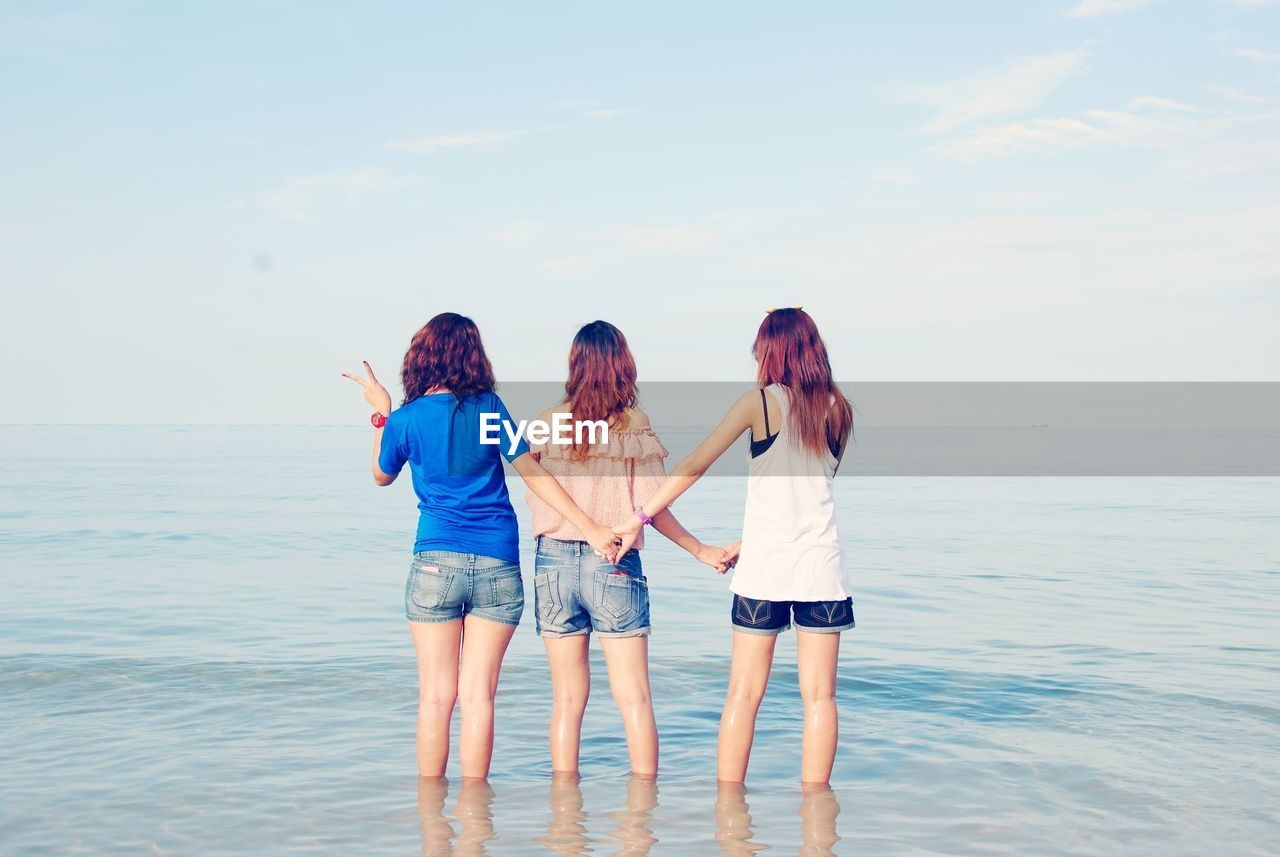 Rear View Of Women Holding Hands While Standing In Sea Against Sky