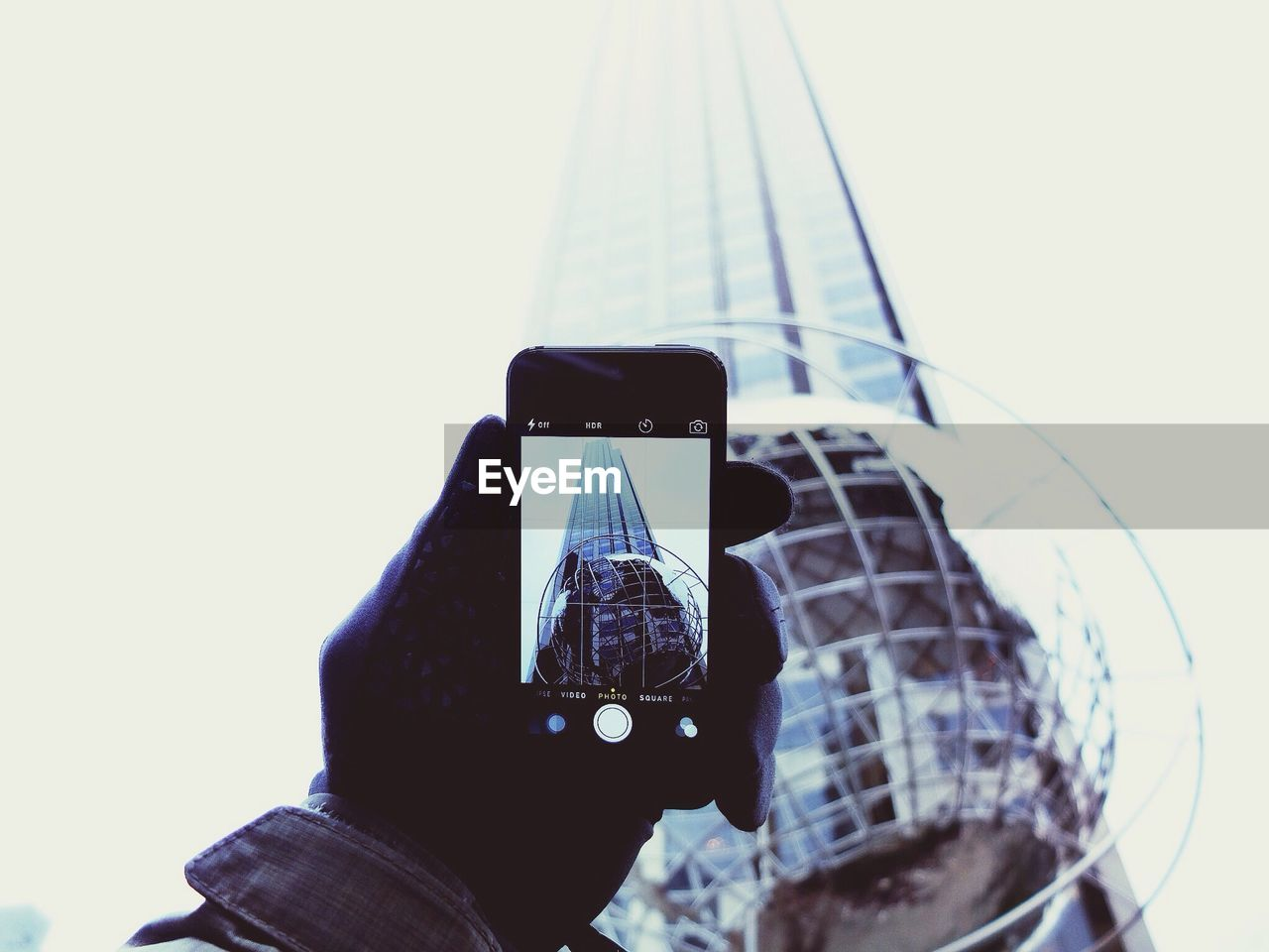 Low angle view of hand photographing skyscraper with mobile phone