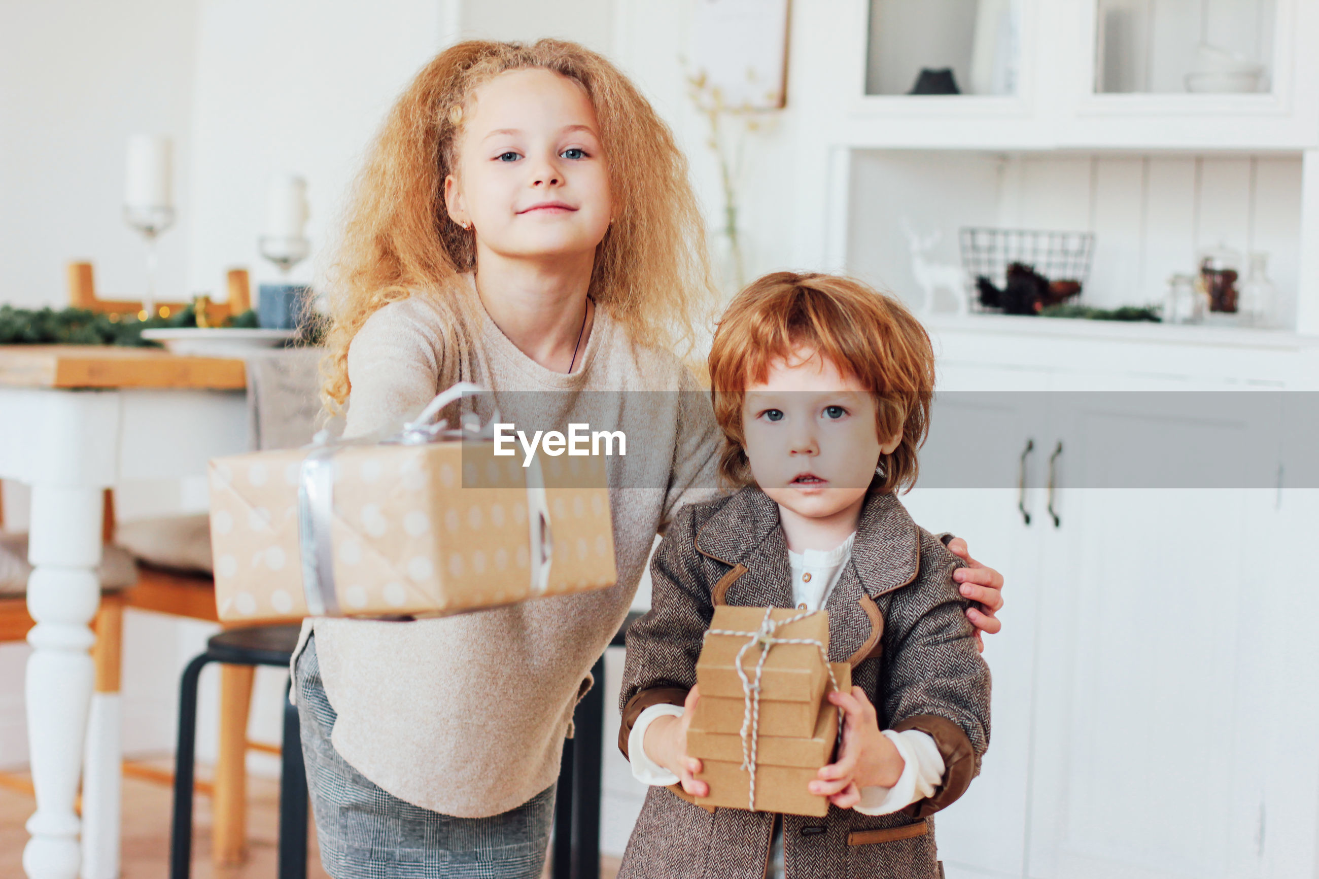 Portrait of cute siblings holding gifts at home